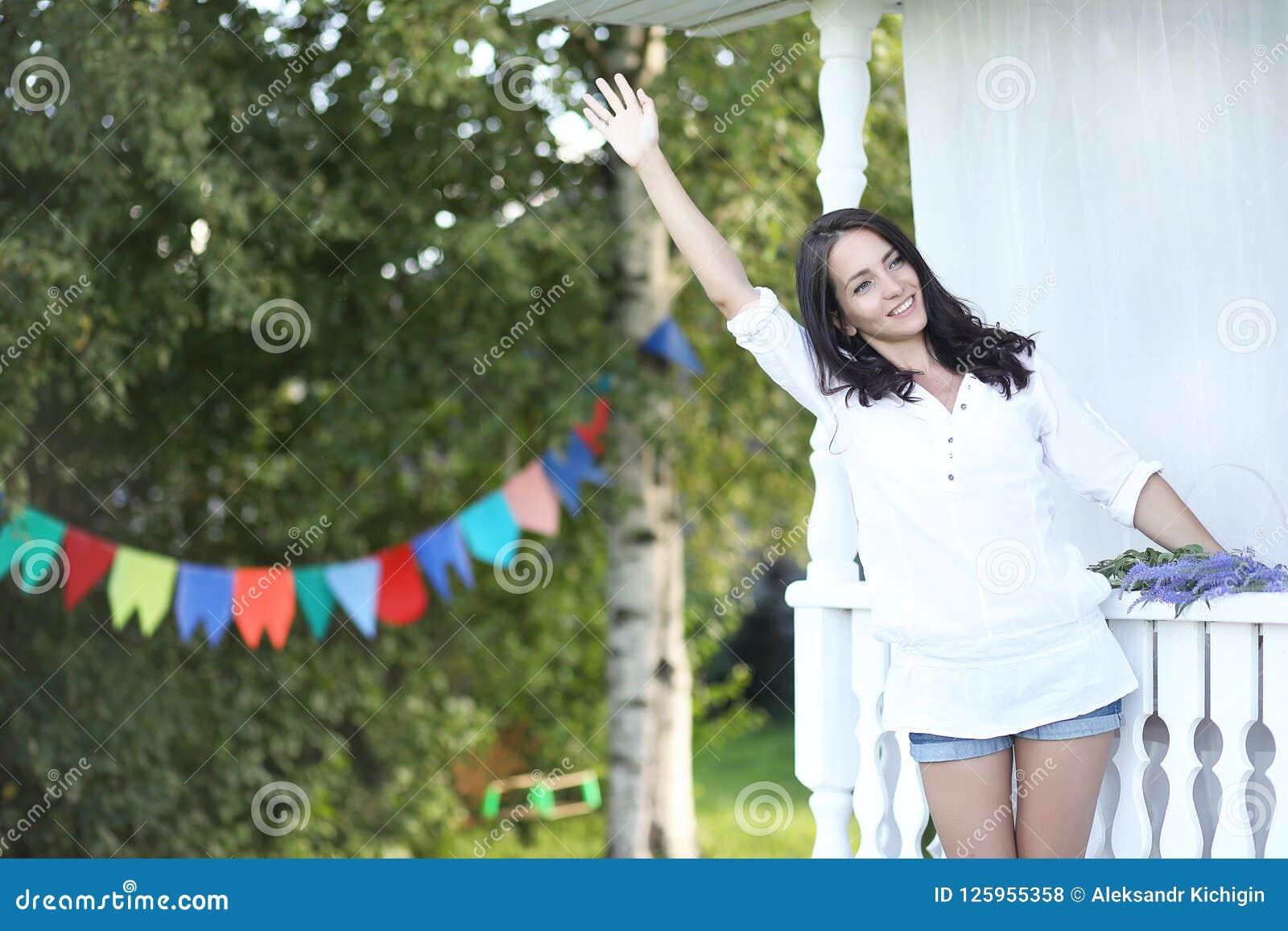 Dziewczyna na drewnianym ganeczku blisko domu