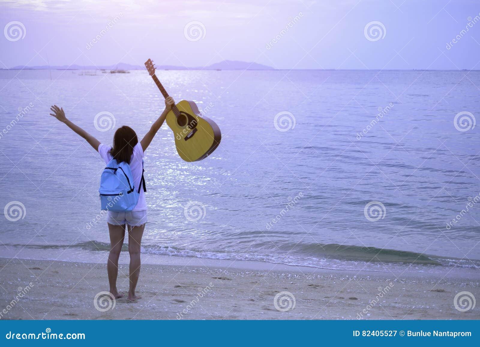 Dziewczyna na plażowym mienie gitary koszt stały, Wakacyjny dziewczyny pojęcie