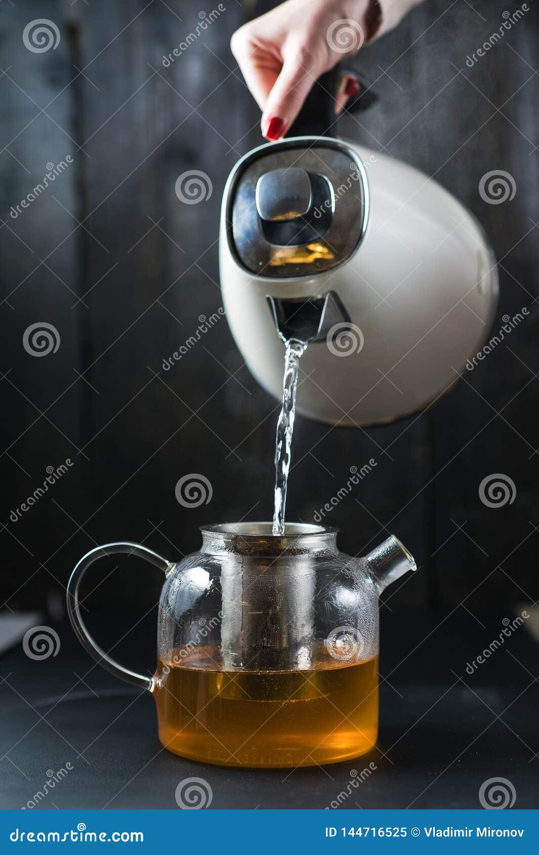 Dziewczyna nalewa wodę w teapot