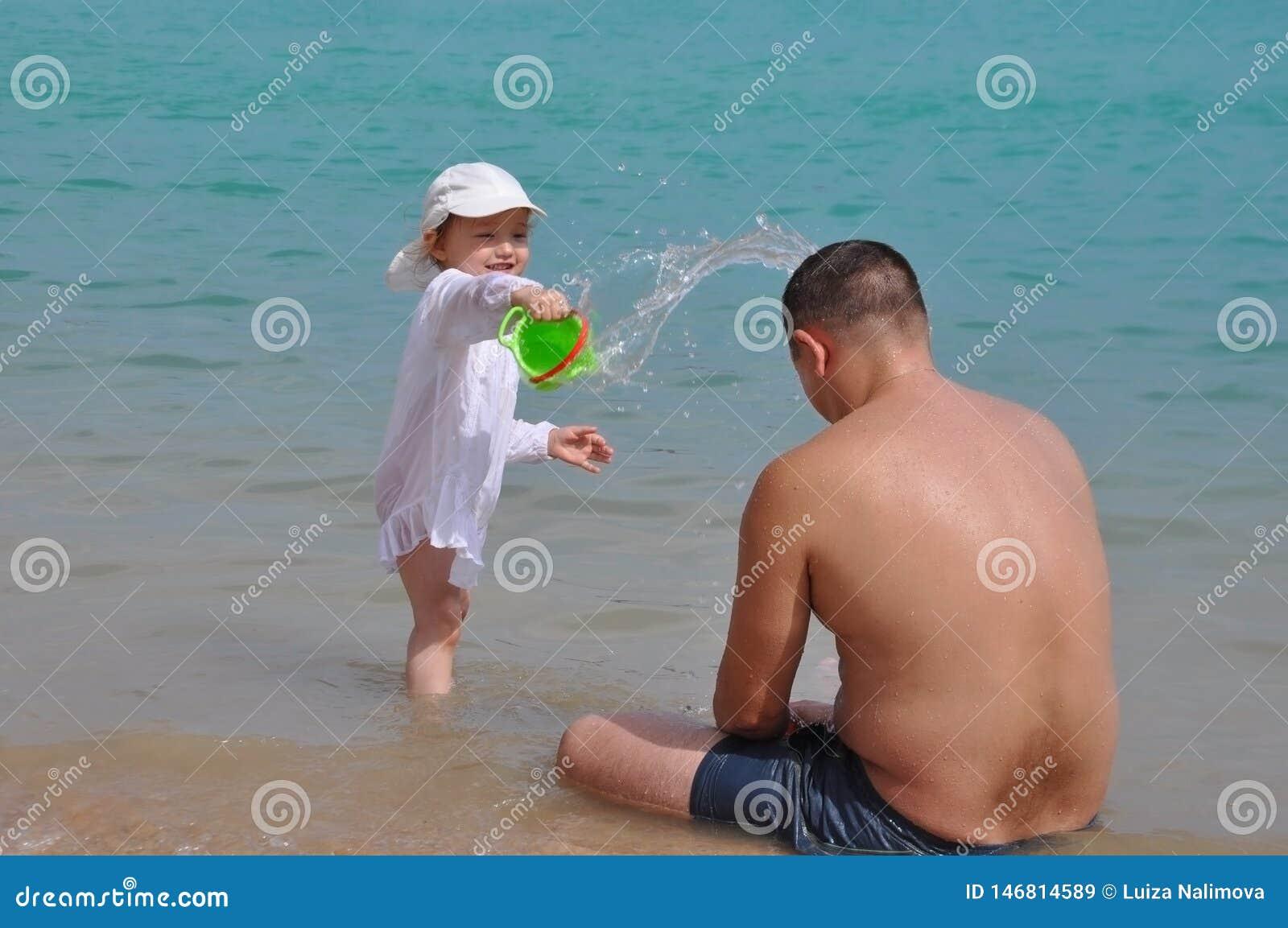 Dziewczyna nalewa wod? na jej ojcu Plu?ni?cia woda w morzu Dziecko i ojciec na wakacje