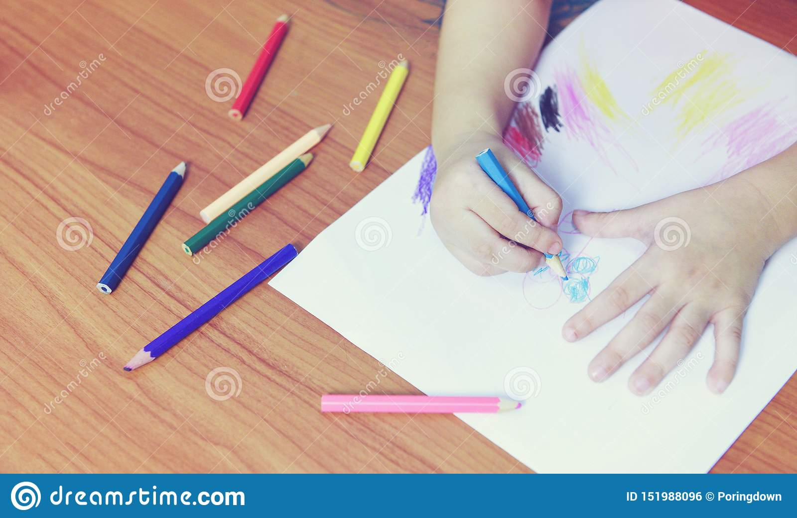 Dziewczyna obraz na papieru prześcieradle z colour ołówkami na drewnianym stołu dziecka dzieciaku robi rysunkowemu obrazkowi i ko