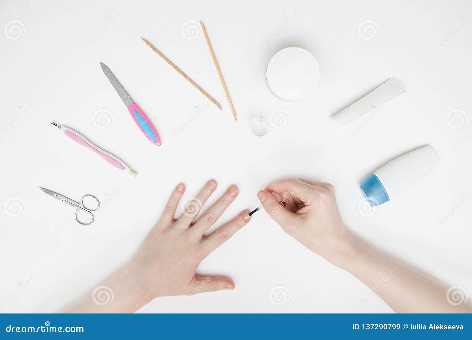 Dziewczyna ono robi manicure owi na białym stole Zakończenie