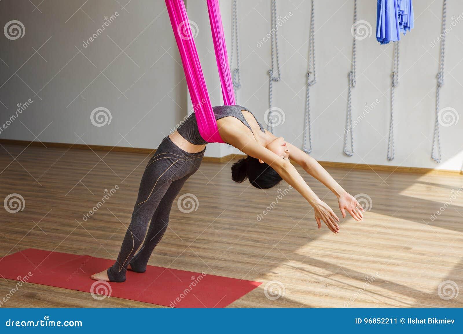 Dziewczyna opiera z powrotem z hamakiem robi powietrznym joga ćwiczeniom