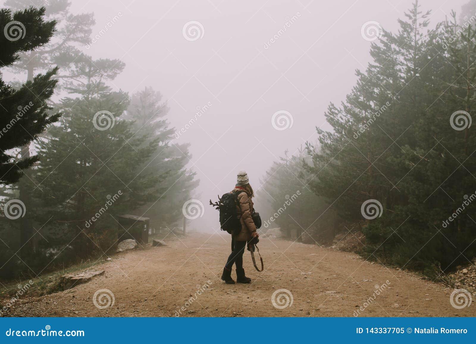 Dziewczyna patrzeje w kierunku gęstej mgły po środku drogi ten przerwa