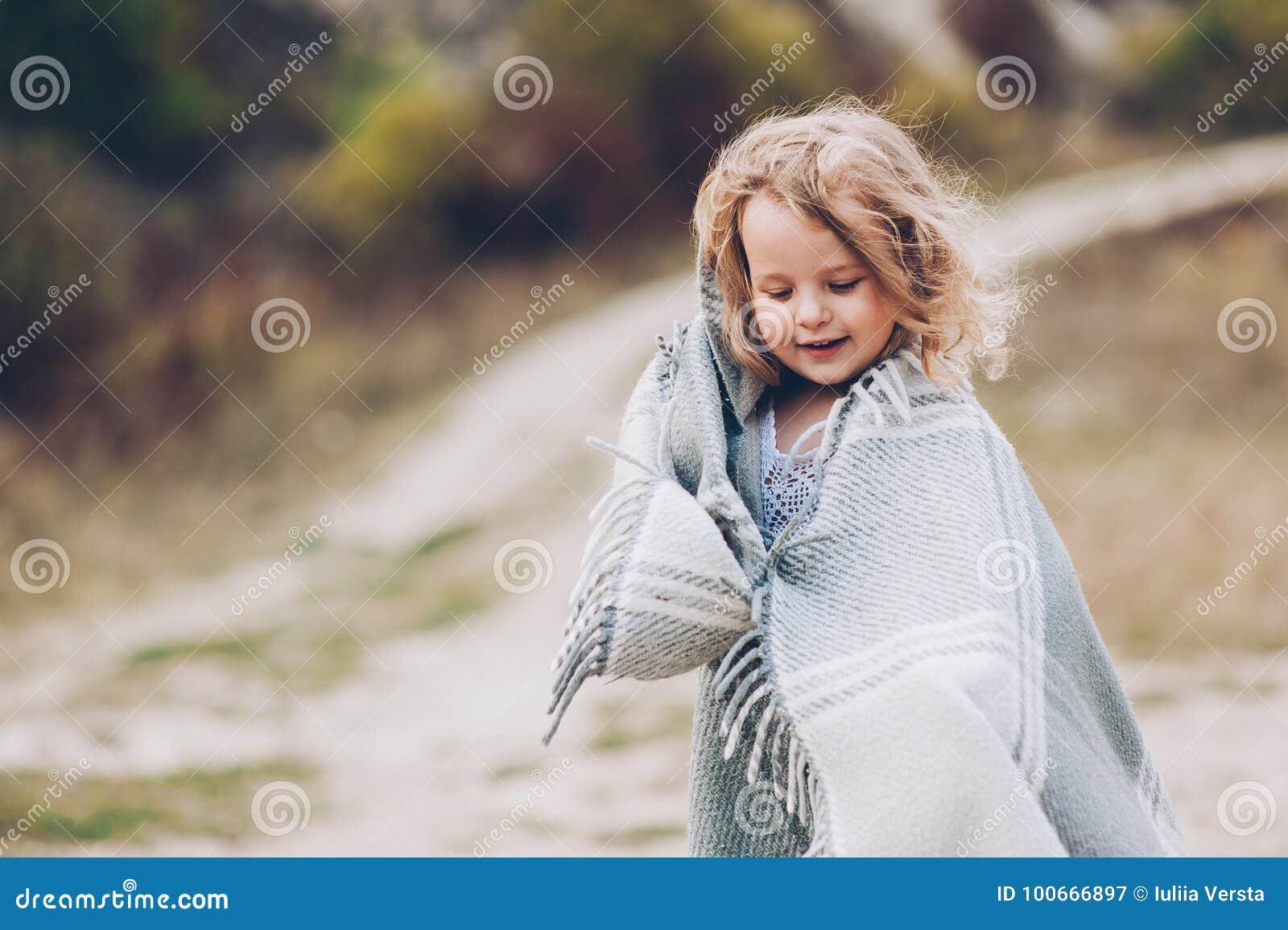 Dziewczyna pobyt zakrywający z koc w parku