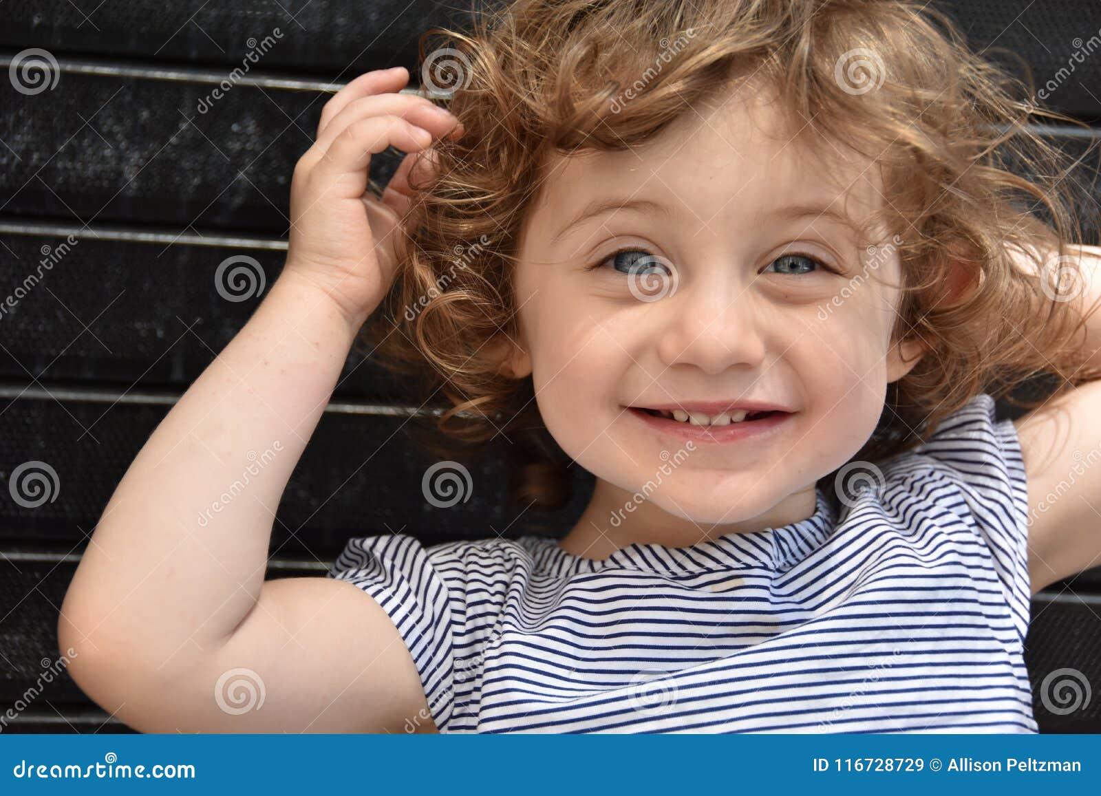 Dziewczyna przeciw czarnemu ściana z cegieł w świetle słonecznym