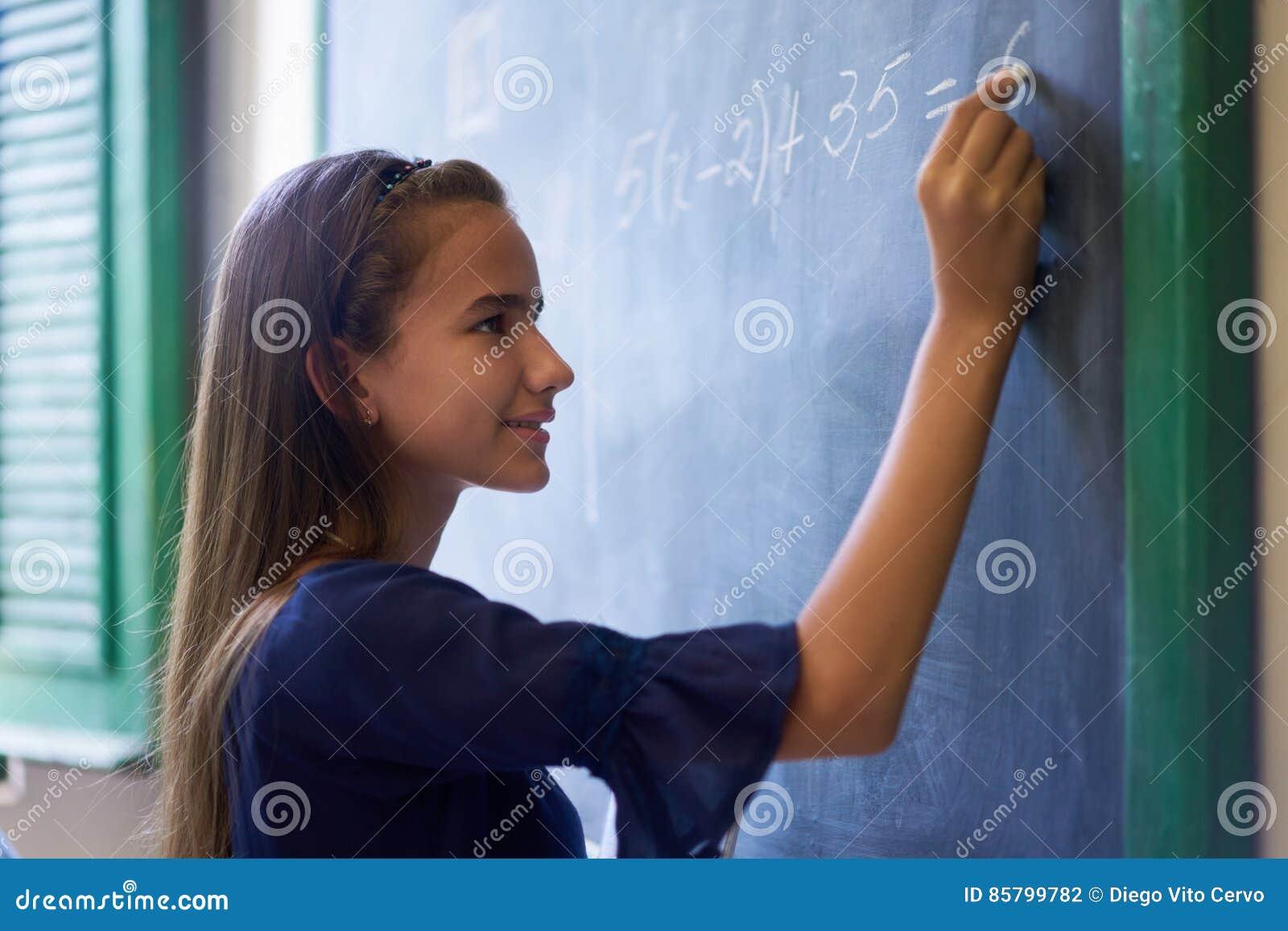 Dziewczyna Robi matematyki ćwiczeniu Przy Blackboard W szkoły średniej klasie