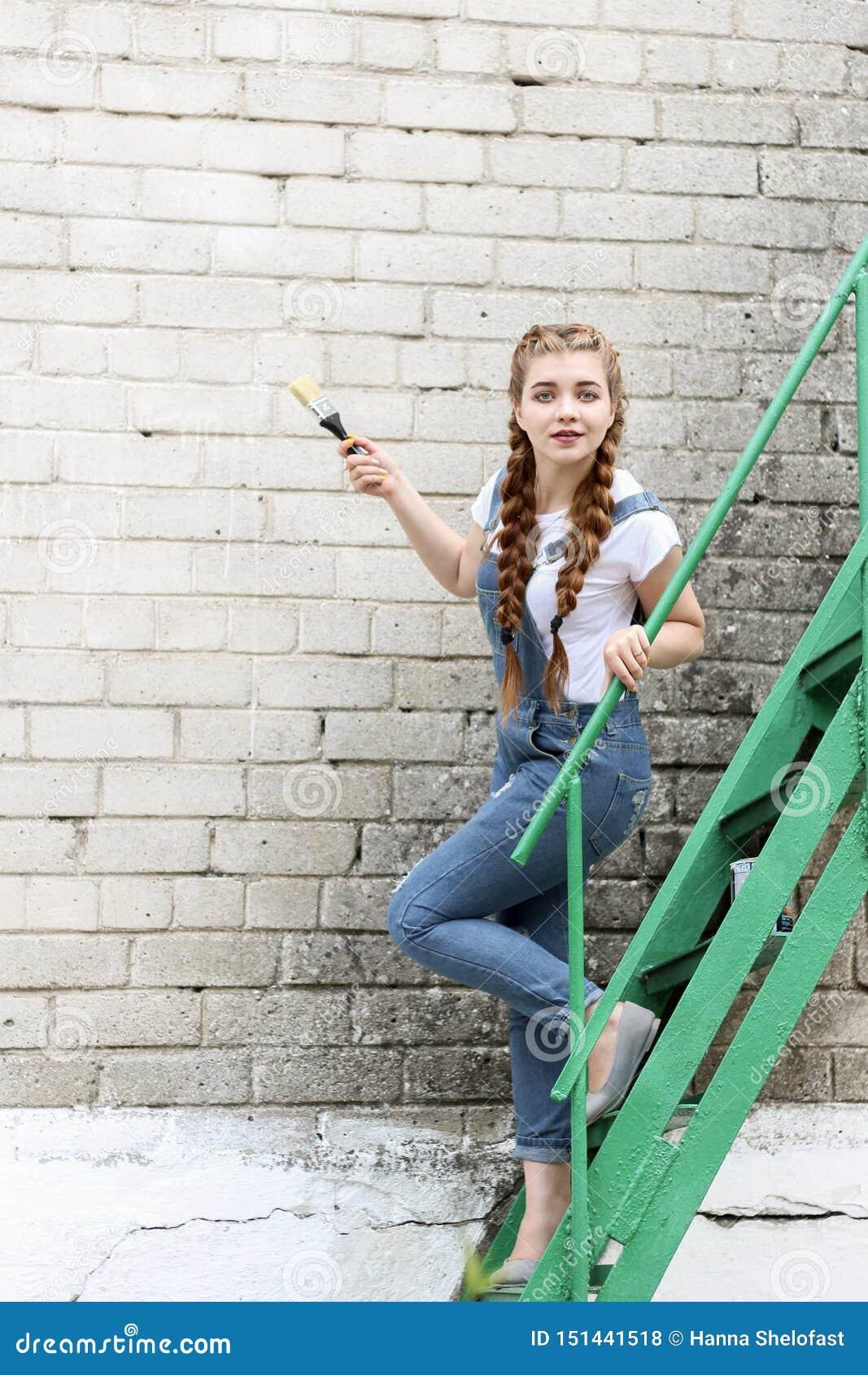 Dziewczyna robi narządzaniu dla malować drewnianego nawierzchniowego gazebo, ogrodzenie