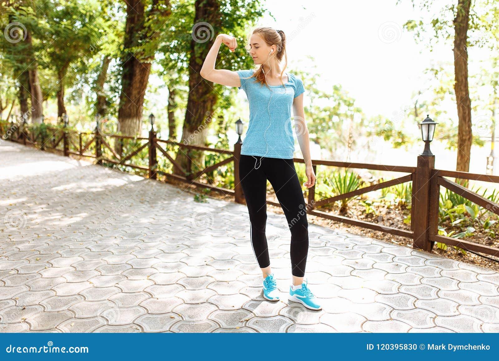 Dziewczyna słucha muzyka w hełmofonach podczas szkolenia, biega w świeżym powietrzu, ranku szkolenie