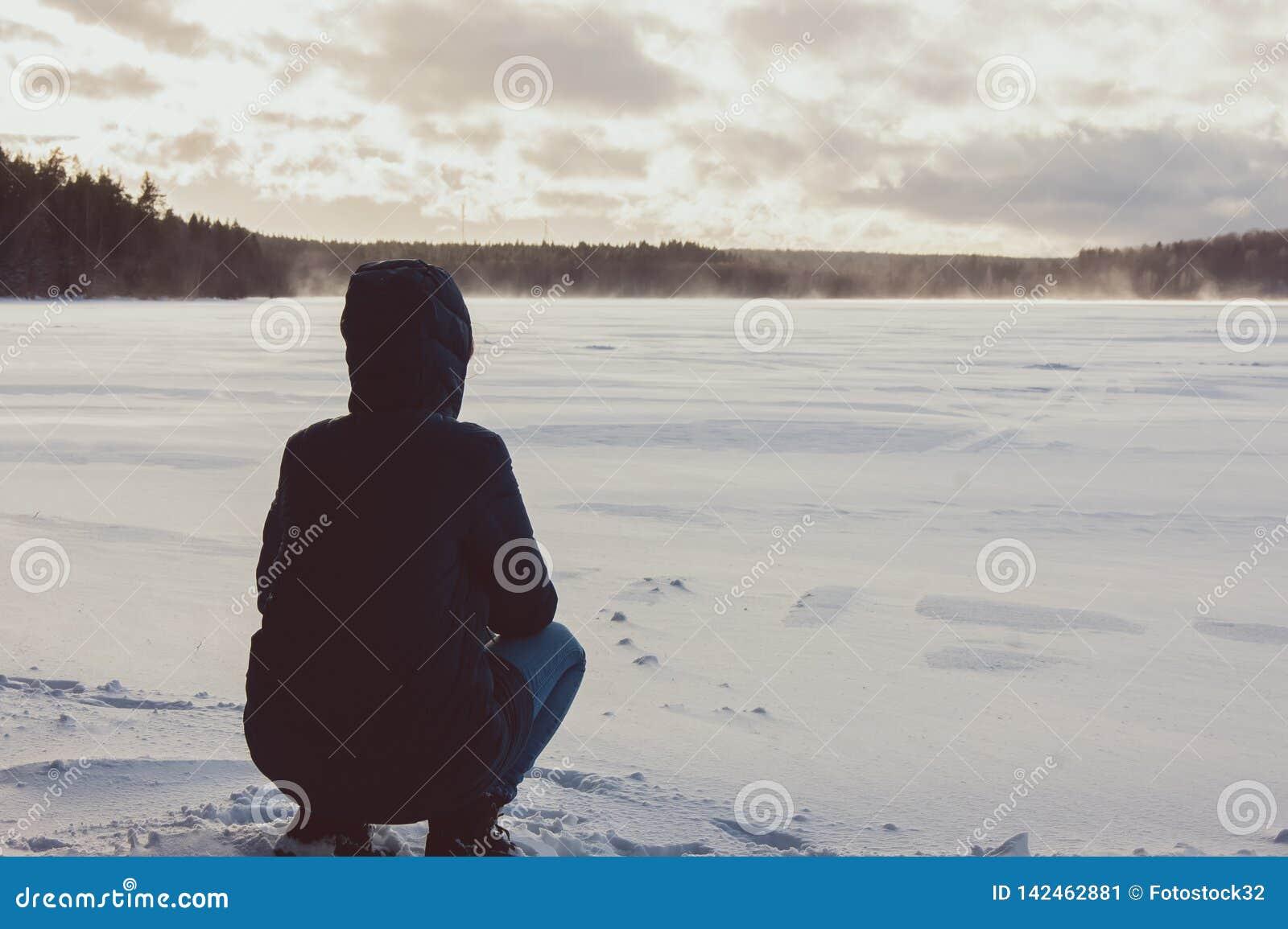 Dziewczyna siedzi na brzeg zimy jezioro