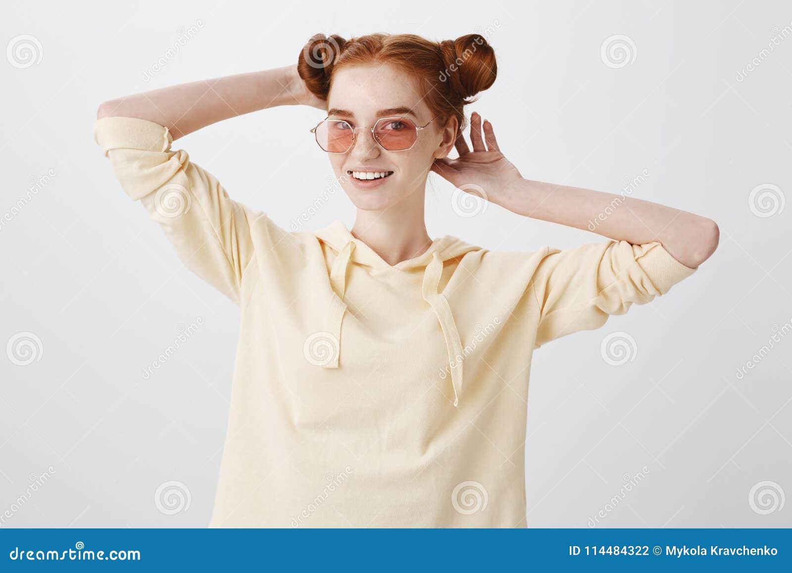 Dziewczyna sprawdza ostrzyżenie, patrzeje w lustrze Studio strzelał elegancki młody żeński uczeń w modnych okularach przeciwsłone