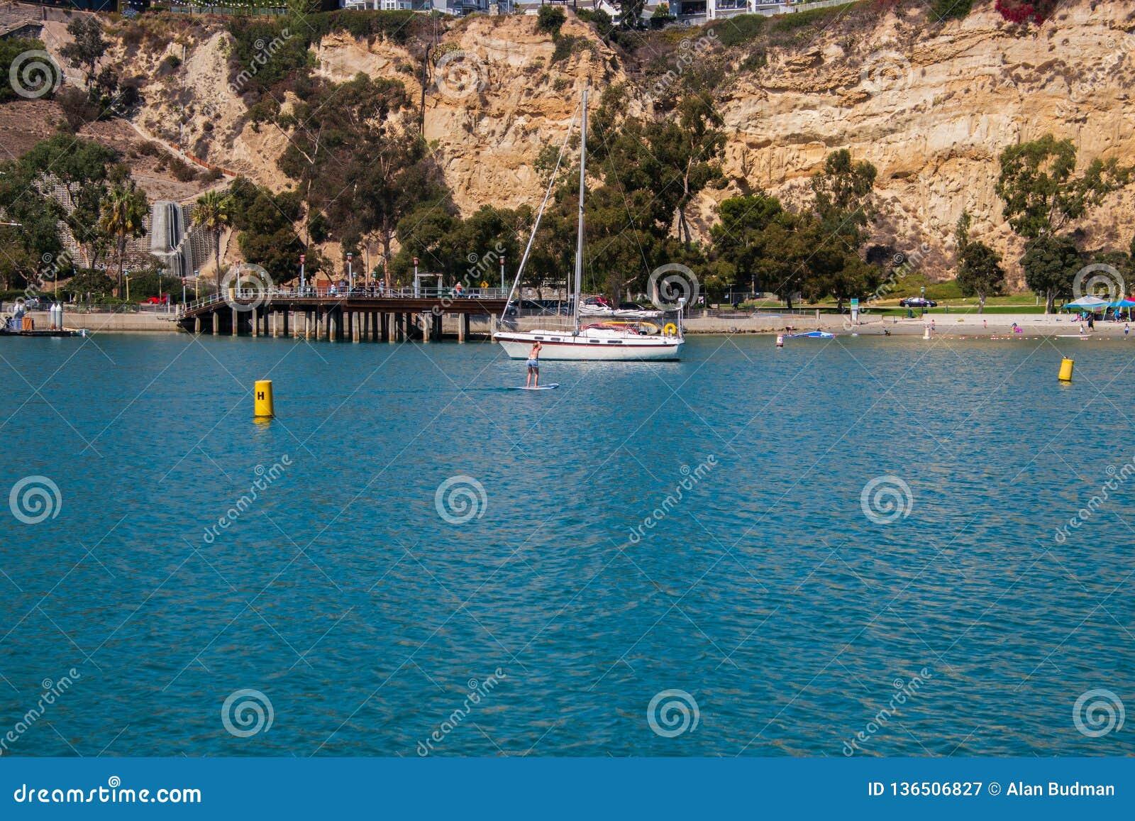 Dziewczyna stoi na paddle desce paddling na gładkiej błękitne wody
