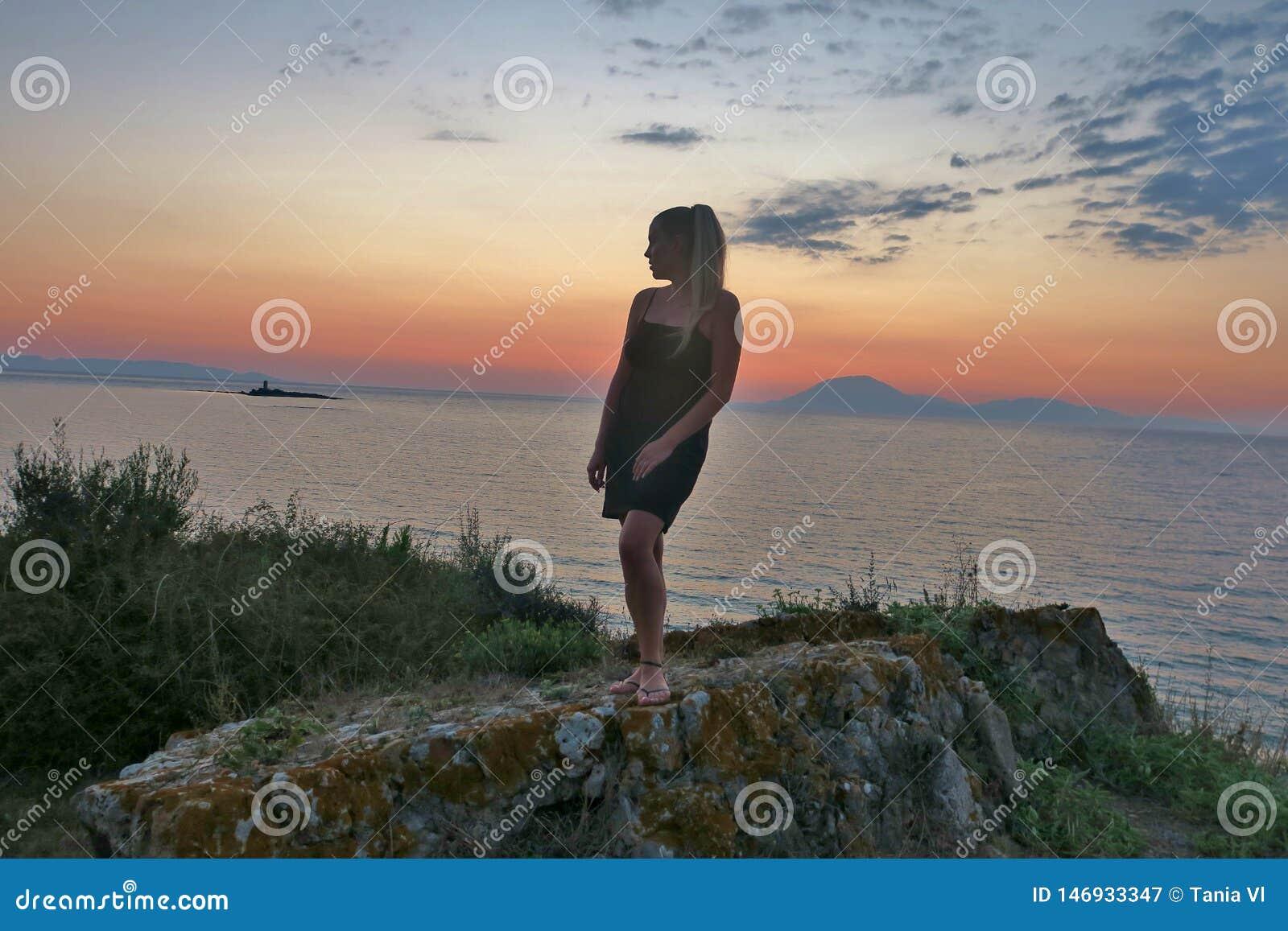 Dziewczyna stojaki na skale i spojrzenia przy pi?knym widokiem zmierzch i morze