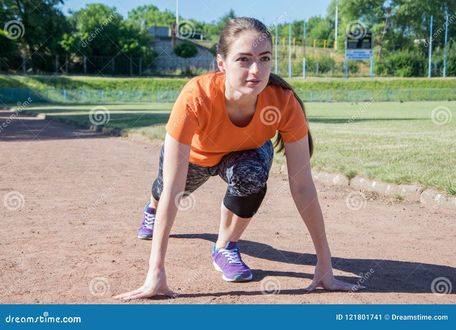 Dziewczyna stojaki przy początkiem przed biegać
