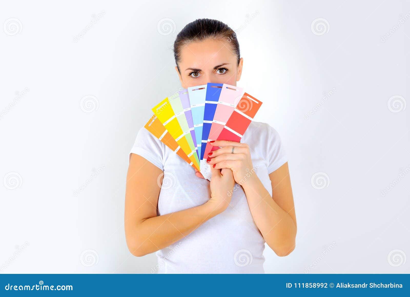 Dziewczyna trzyma fan w jej rękach wybierać farbę