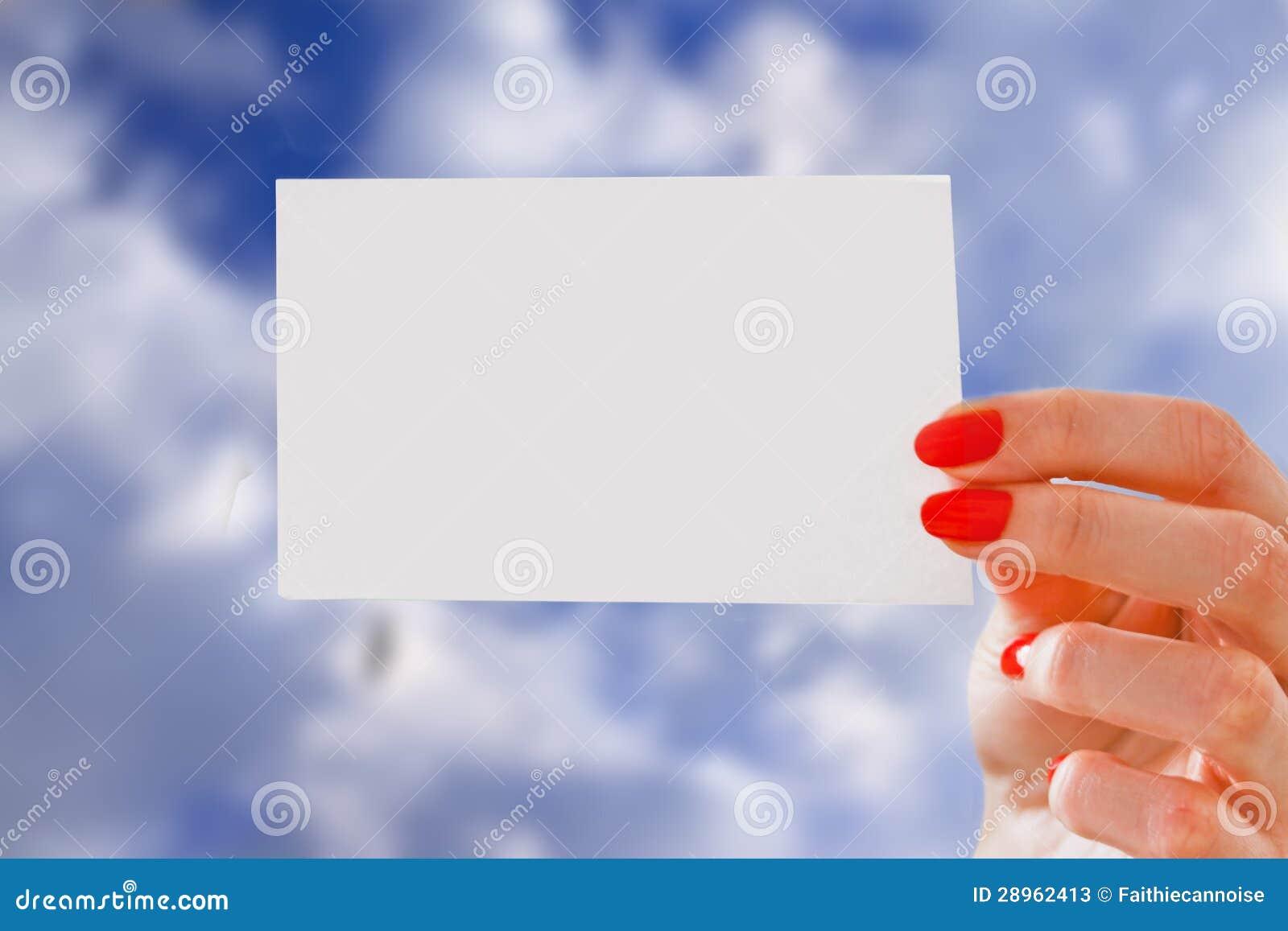 Dziewczyna trzyma kawałek papieru z copyspace nad niebieskim niebem