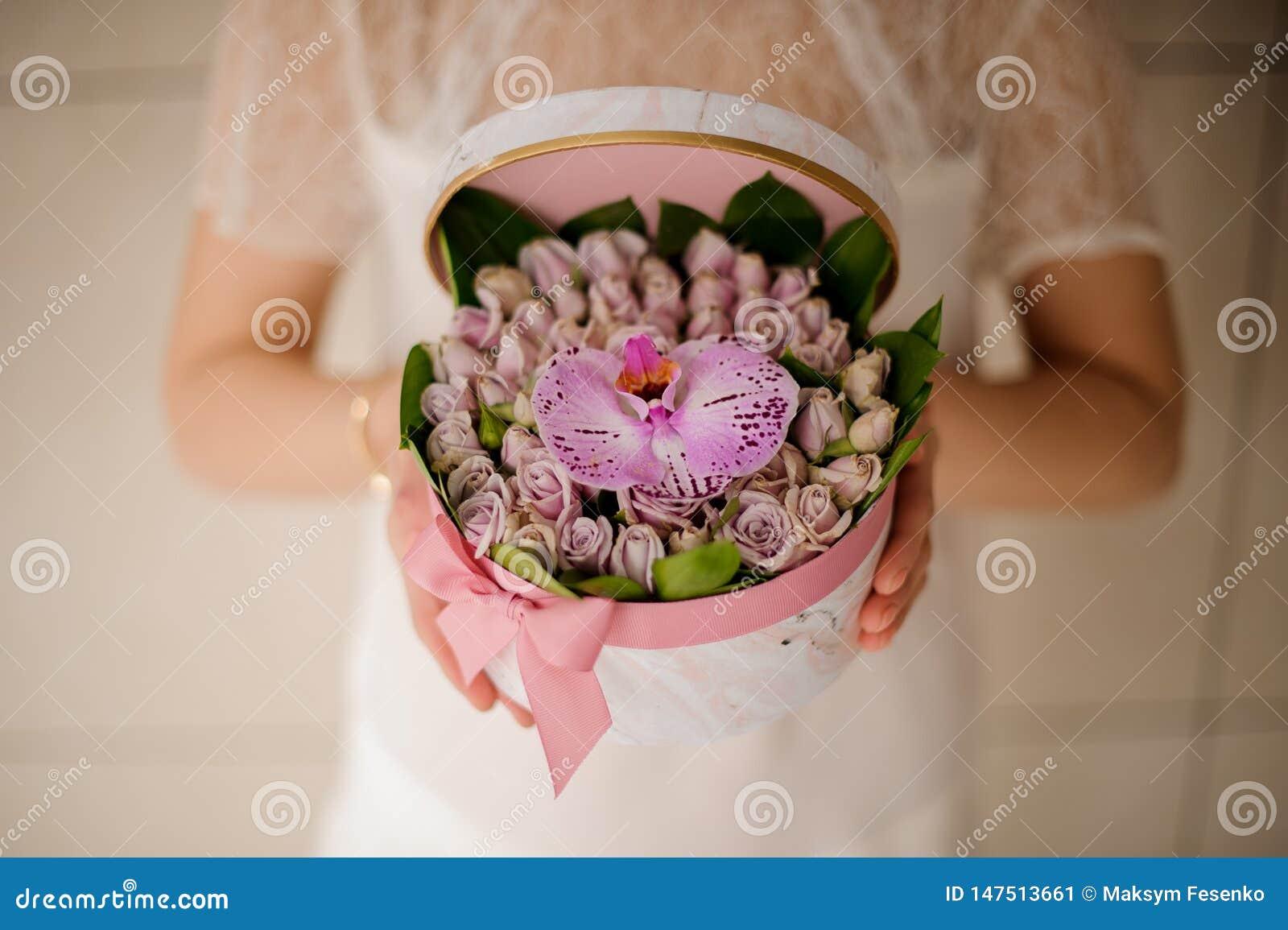Dziewczyna trzyma małego kapeluszu pudełko z ślubnym bukietem