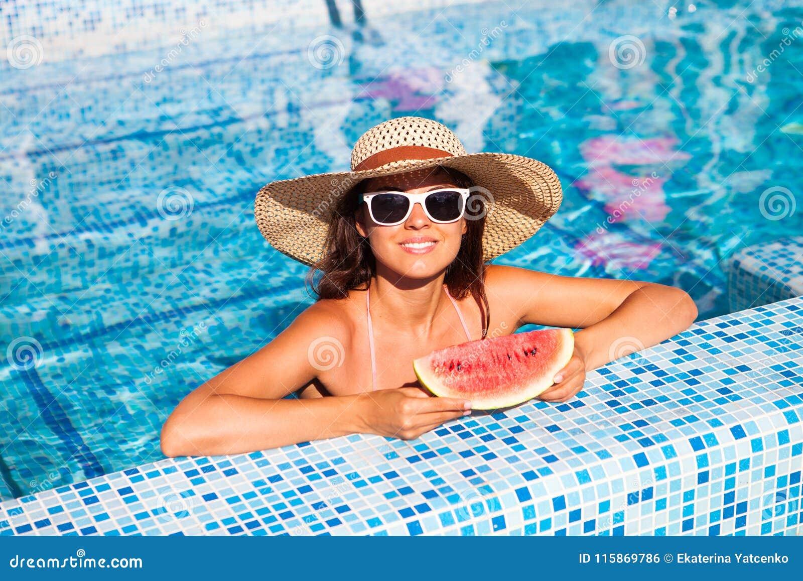 Dziewczyna trzyma połówkę czerwonego arbuza nad błękitnym basenem, relaksuje o