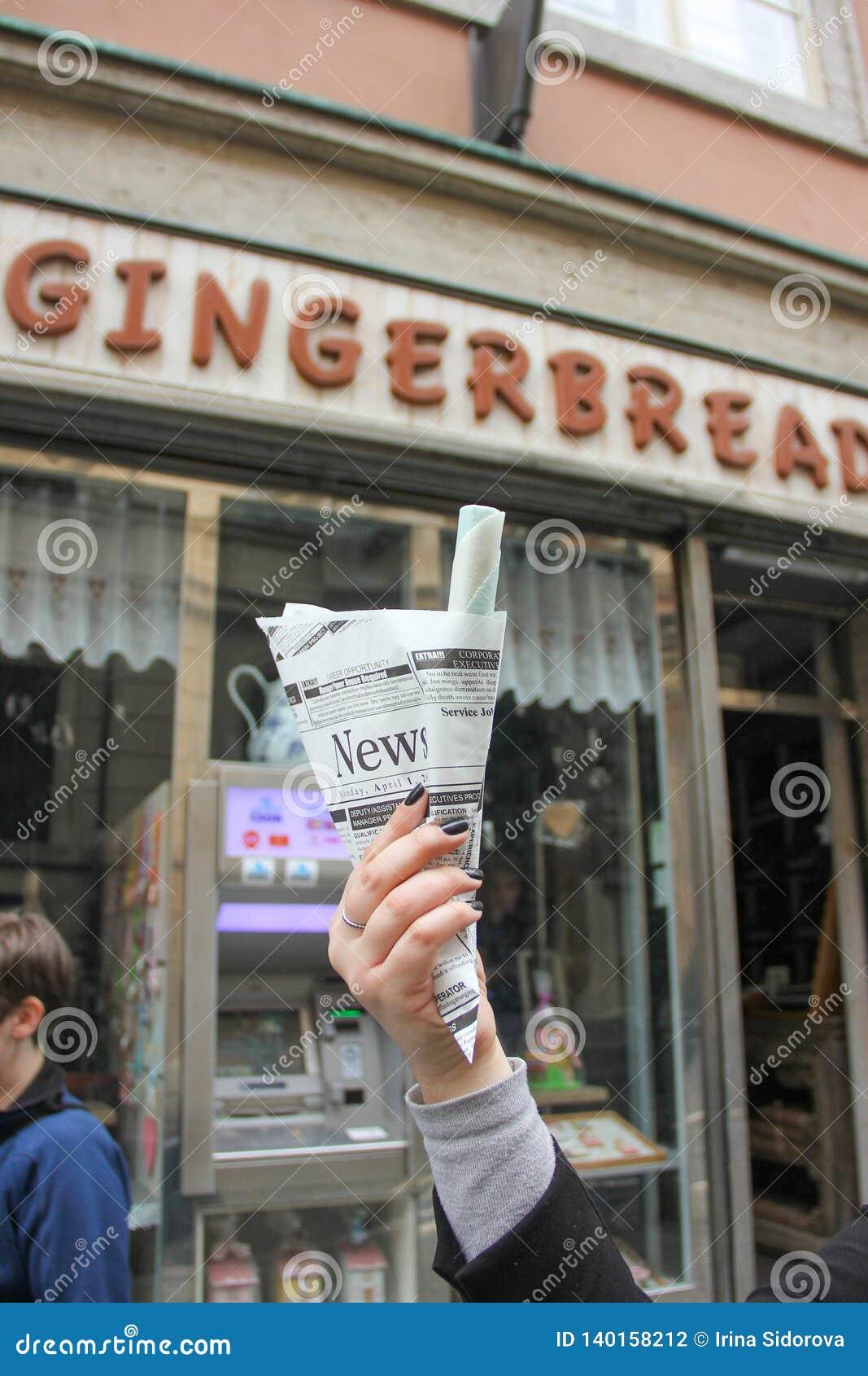Dziewczyna trzyma słodką pamiątkarską opłatek rolkę w gazecie na tle gingerbreas kawiarni sklep