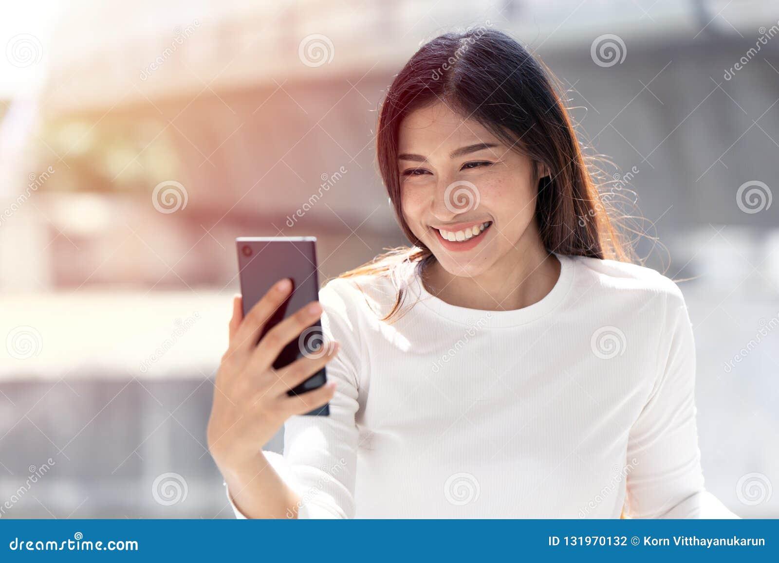 Dziewczyna uśmiechu przyglądający mądrze telefon dzwoni ekran dla selfie lub wideo wezwania