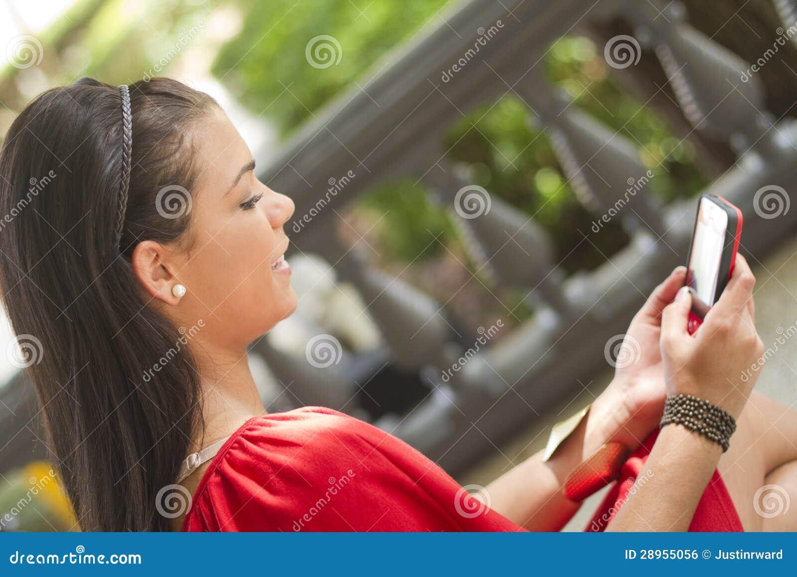 Dziewczyna używa jej telefon komórkowy wiadomość tekstowa