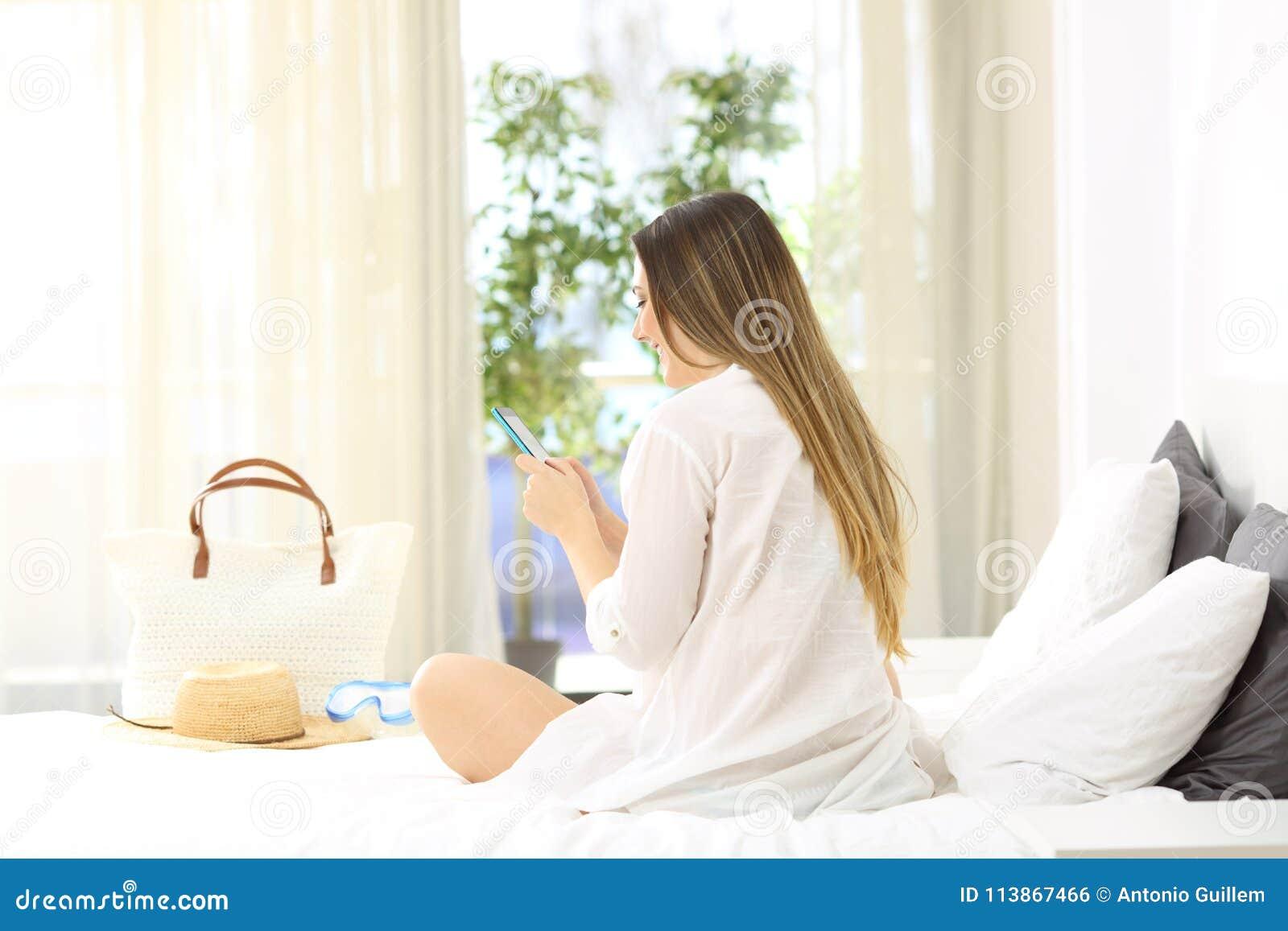 Dziewczyna używa mądrze telefon na łóżku w wakacjach
