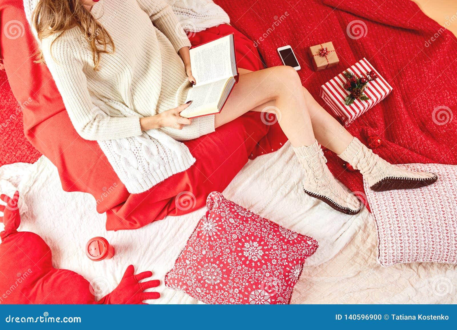Dziewczyna ubierająca dział skarpet kłamstwa, czyta książkę na i białych poduszkach z i koc, czerwona filiżanka smokingowych i tr
