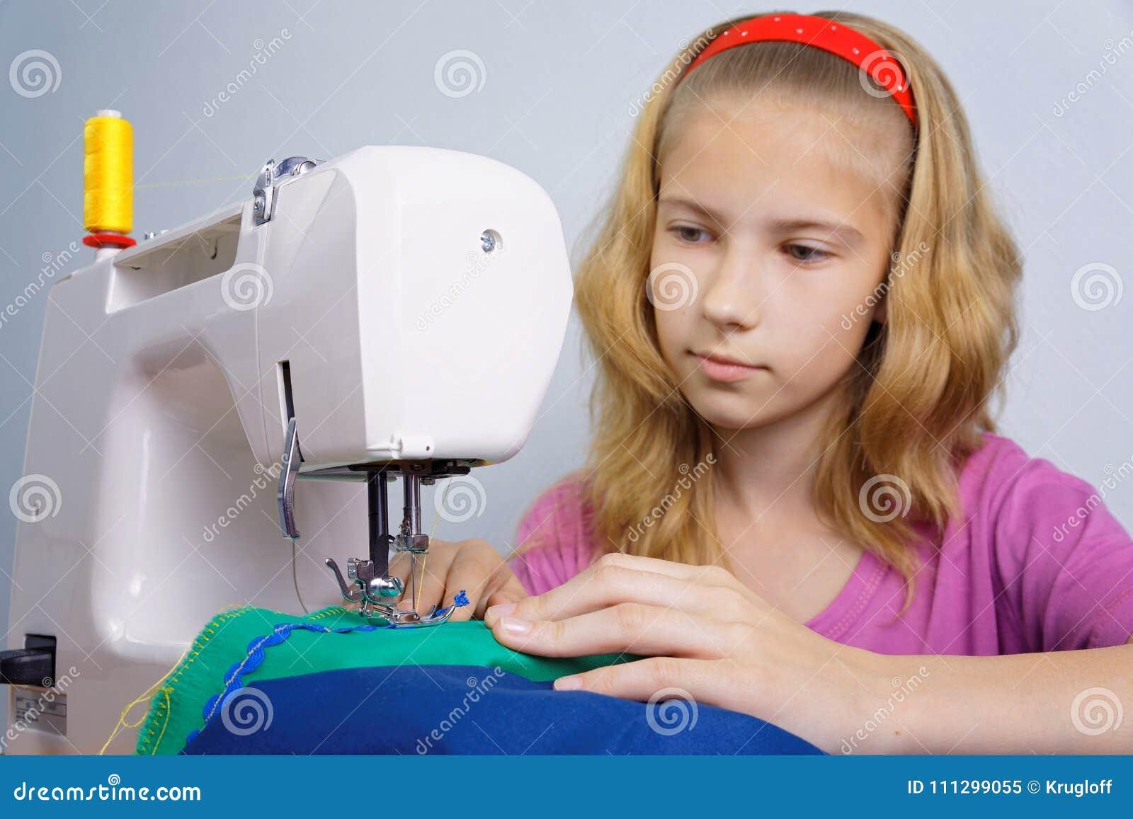 Dziewczyna uczy się szyć na elektrycznej szwalnej maszynie