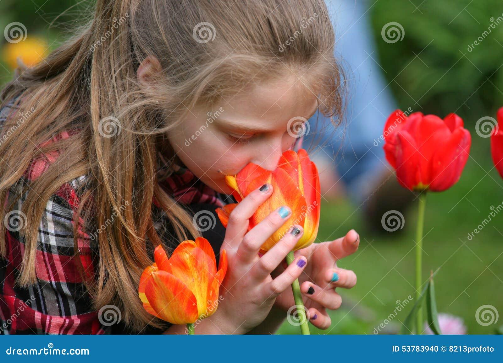 Dziewczyna wącha kwiaty w ogródzie