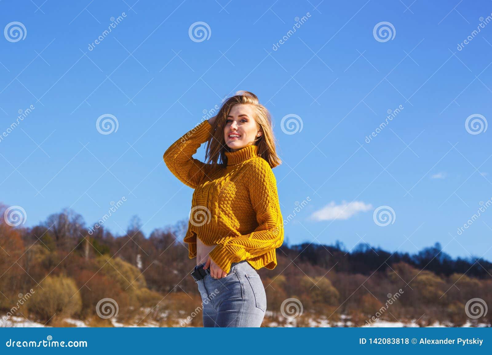 Dziewczyna w żółtym pulowerze pozuje przeciw zima lasowi i niebieskiemu niebu
