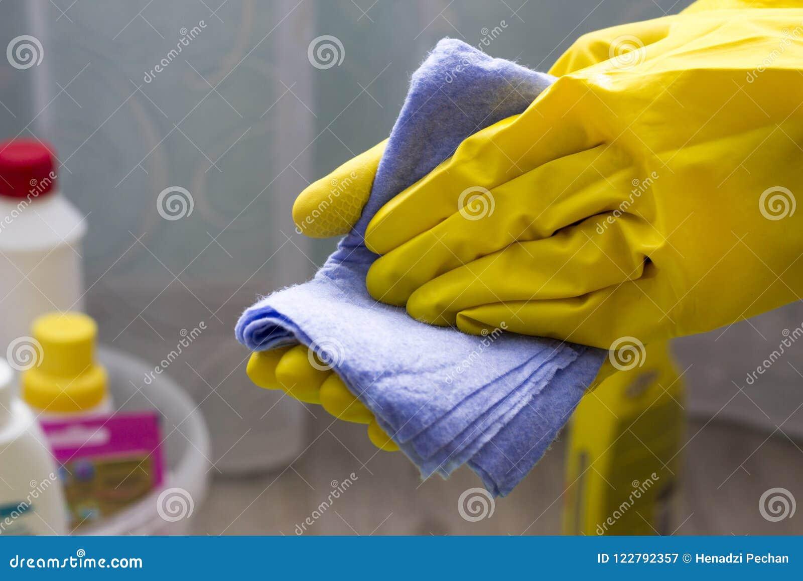 Dziewczyna w żółtych rękawiczkach trzyma łachman, zakończenia sprzątanie