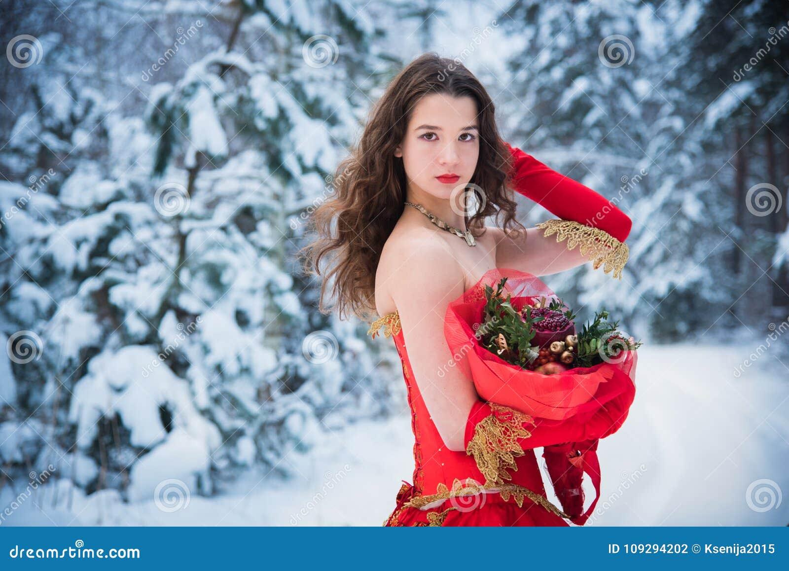Dziewczyna w baśniowym wizerunku królowej pozy w śnieżystego zima lasu czerwieni Długiej sukni, bukiet owoc, czerwoni jabłka