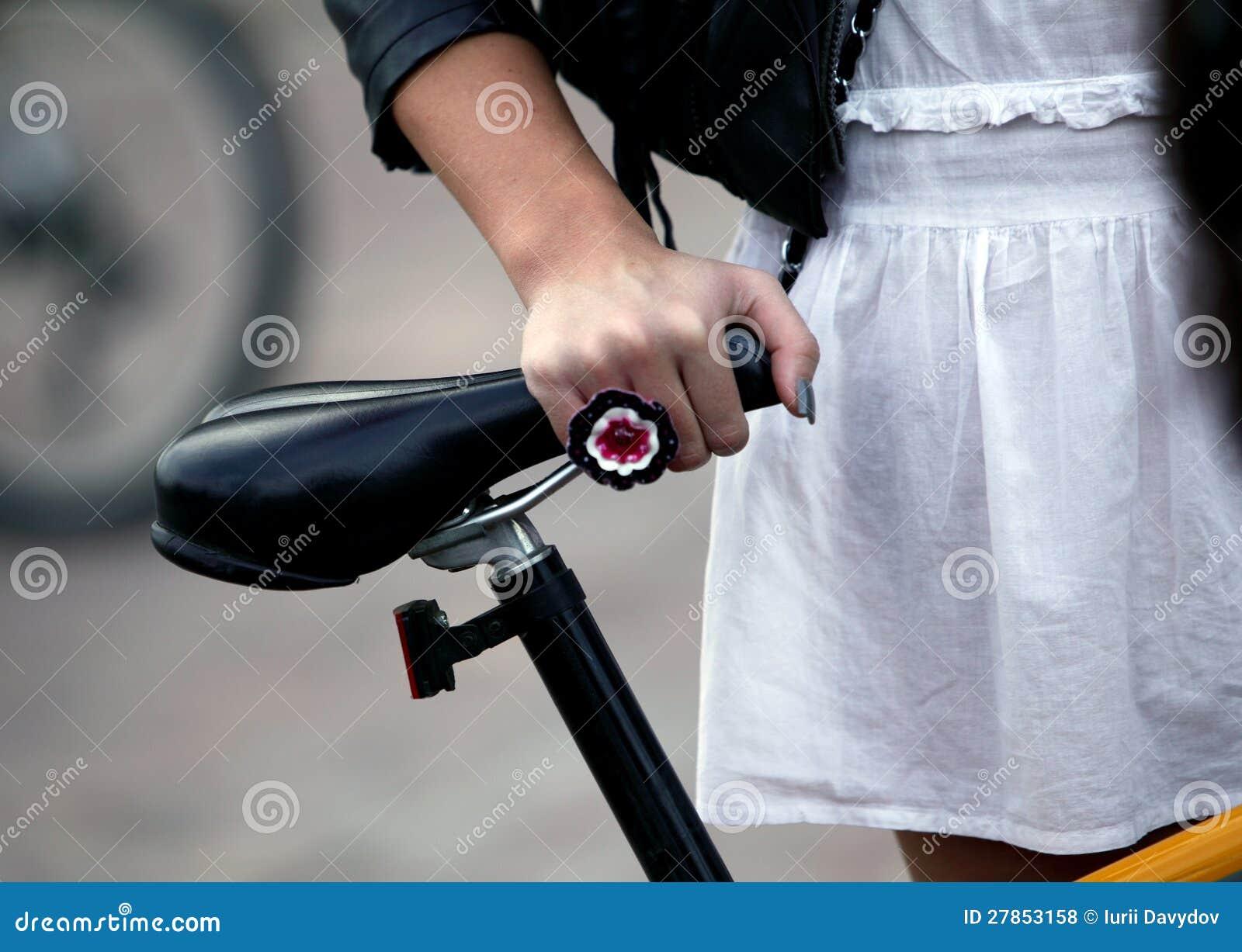 Dziewczyna w białej sukni z stać blisko roweru