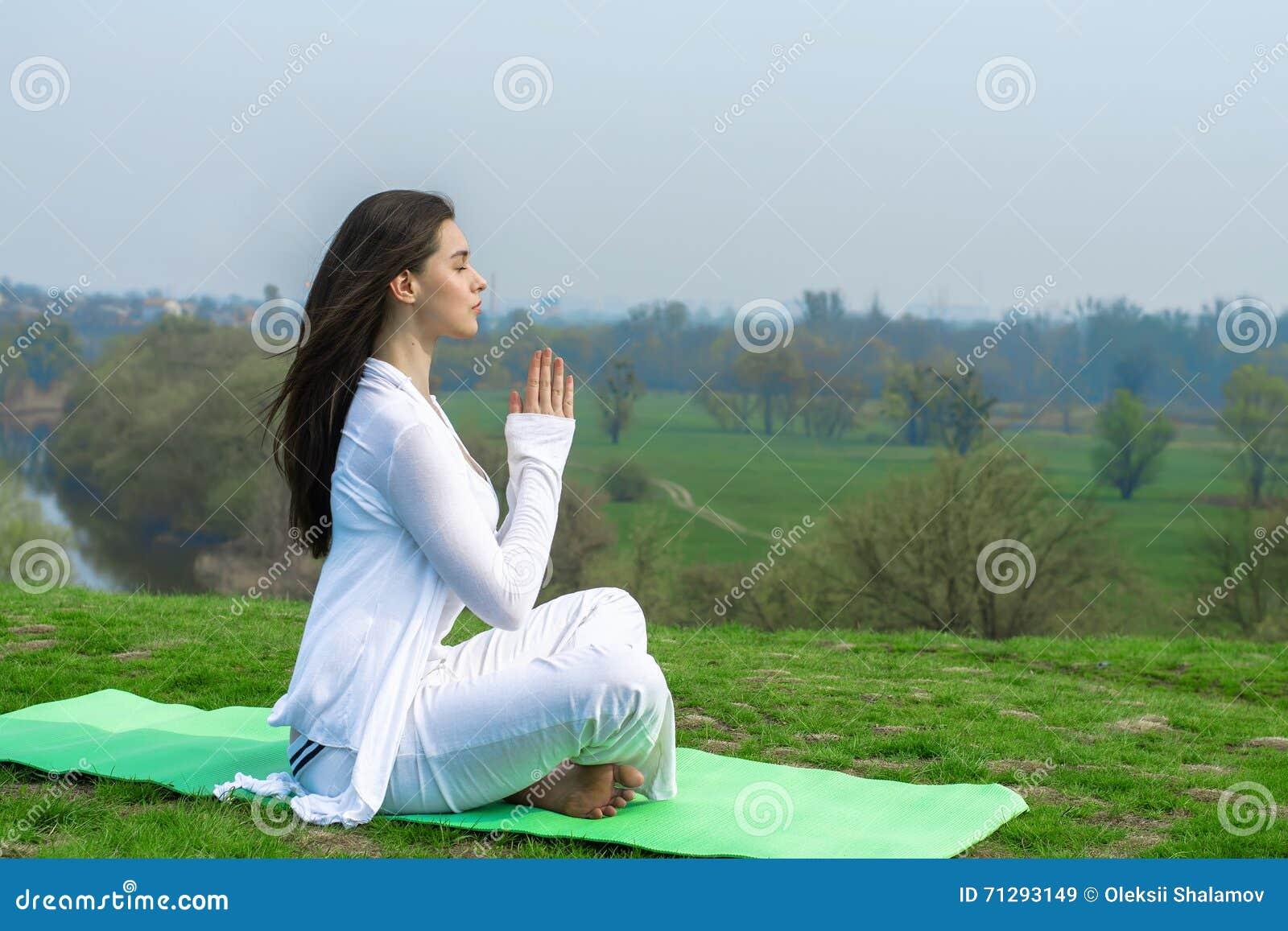 Dziewczyna w biel ubraniach robi joga ćwiczeniom
