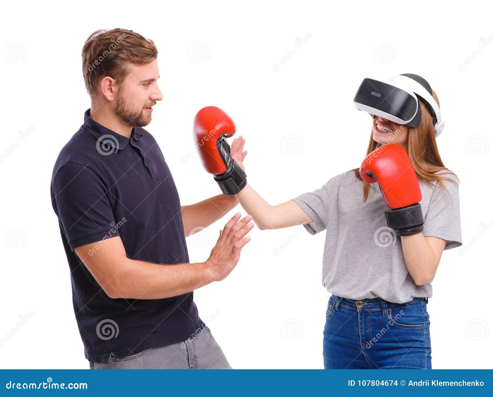 Dziewczyna w bokserskich rękawiczek i rzeczywistość wirtualna szkieł rytmach obok trwanie faceta Odizolowywający na bielu