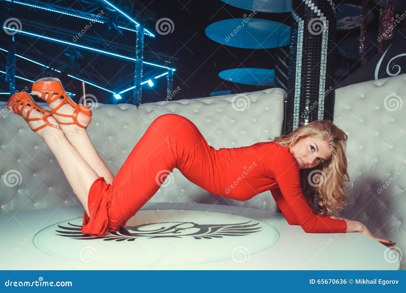 Dziewczyna w czerwieni sukni na stole