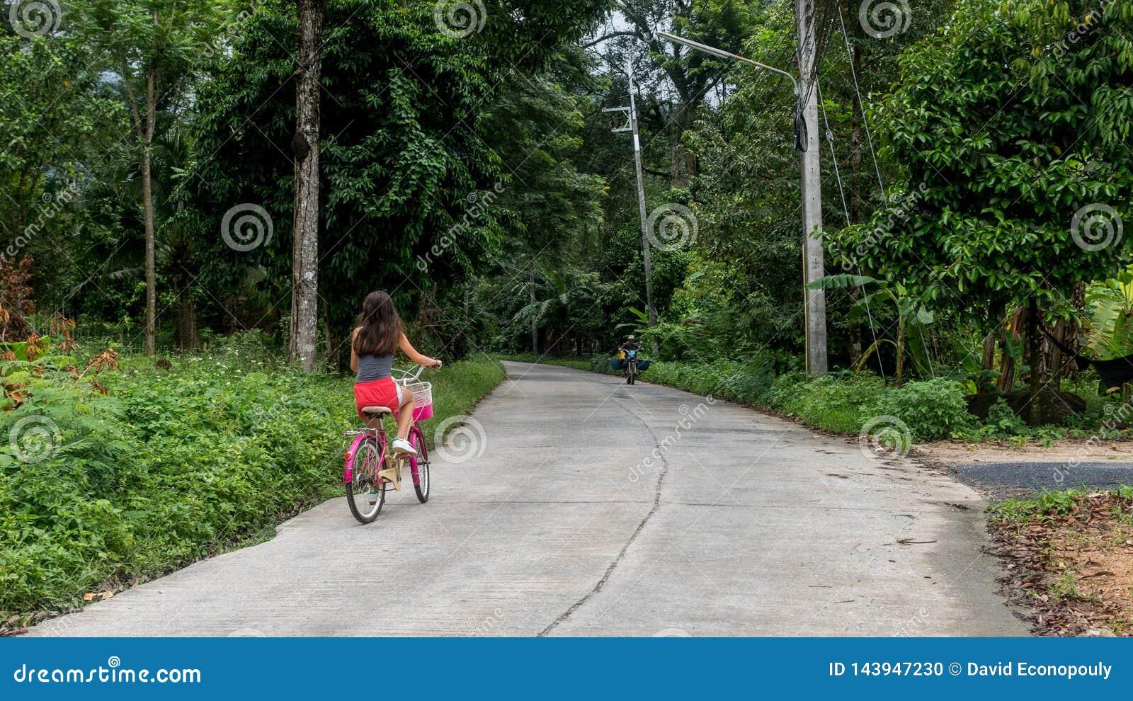 Dziewczyna w czerwieni zwiera je?dzieckiego bicykl