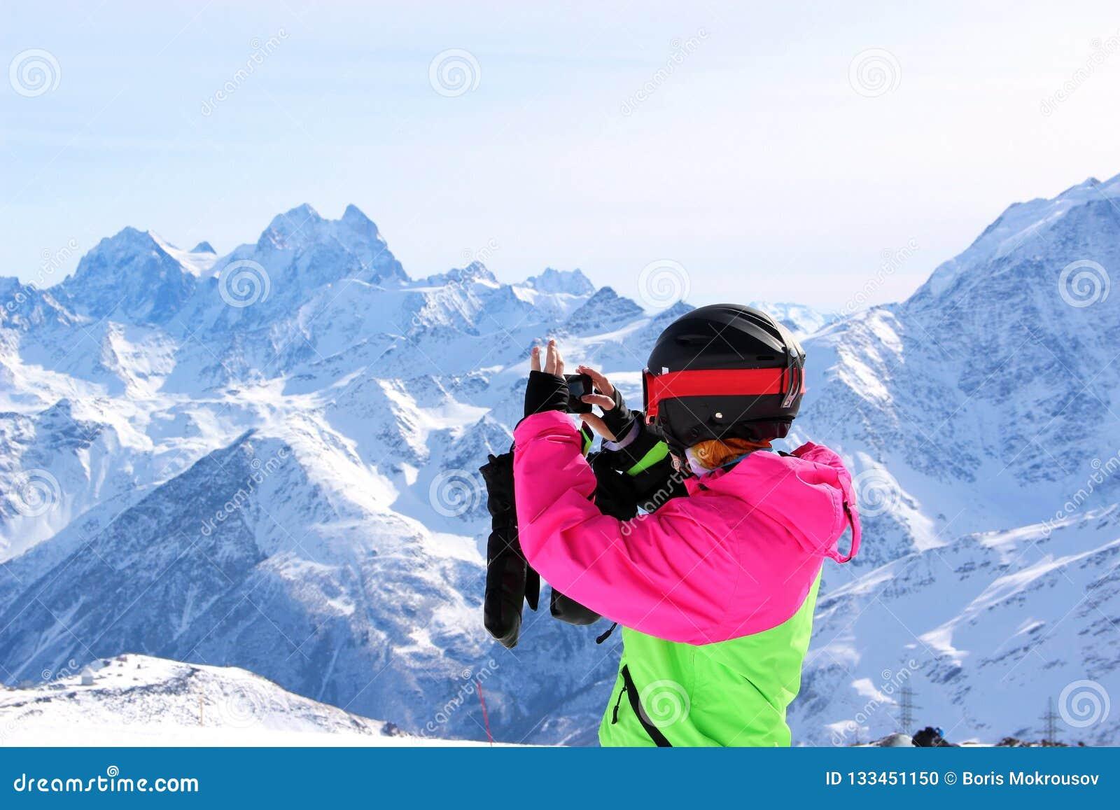 Dziewczyna w kolorowym kostiumu fotografującym na górze śnieżnej góry