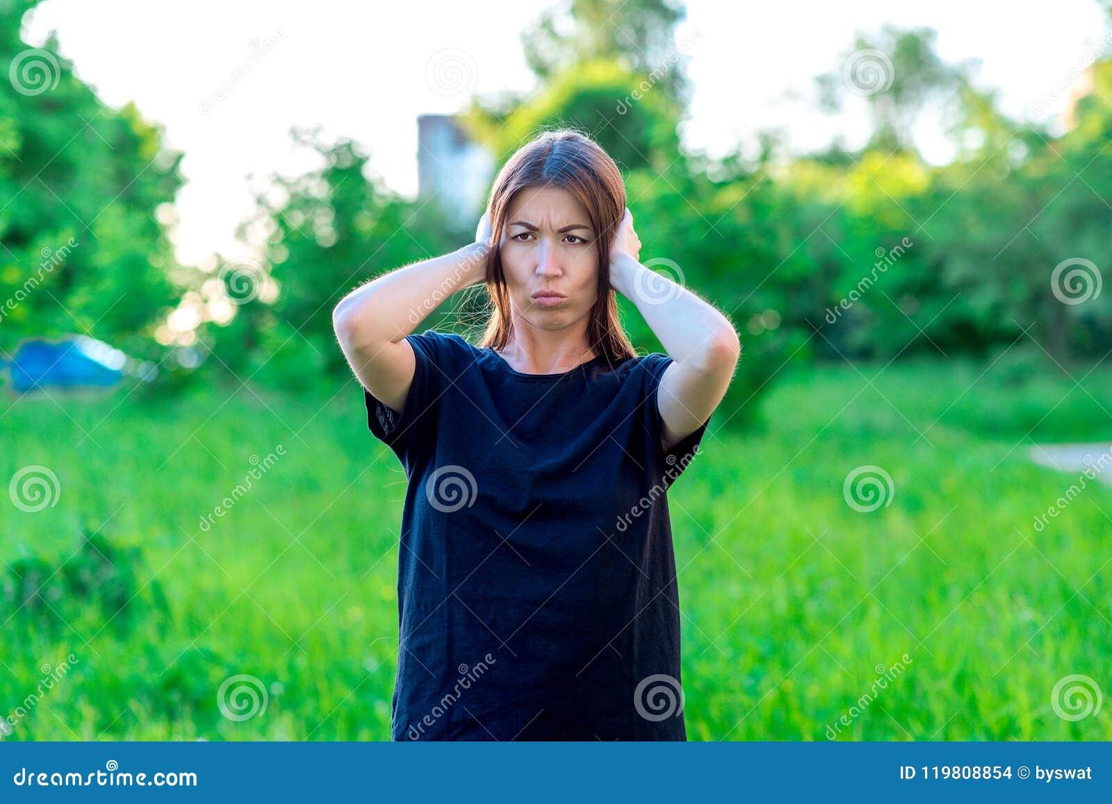 Dziewczyna w lecie w parku w czarnej koszulce azjaci piękna Zakrywa jego ucho z jego rękami Emocjonalnie głośny hałas