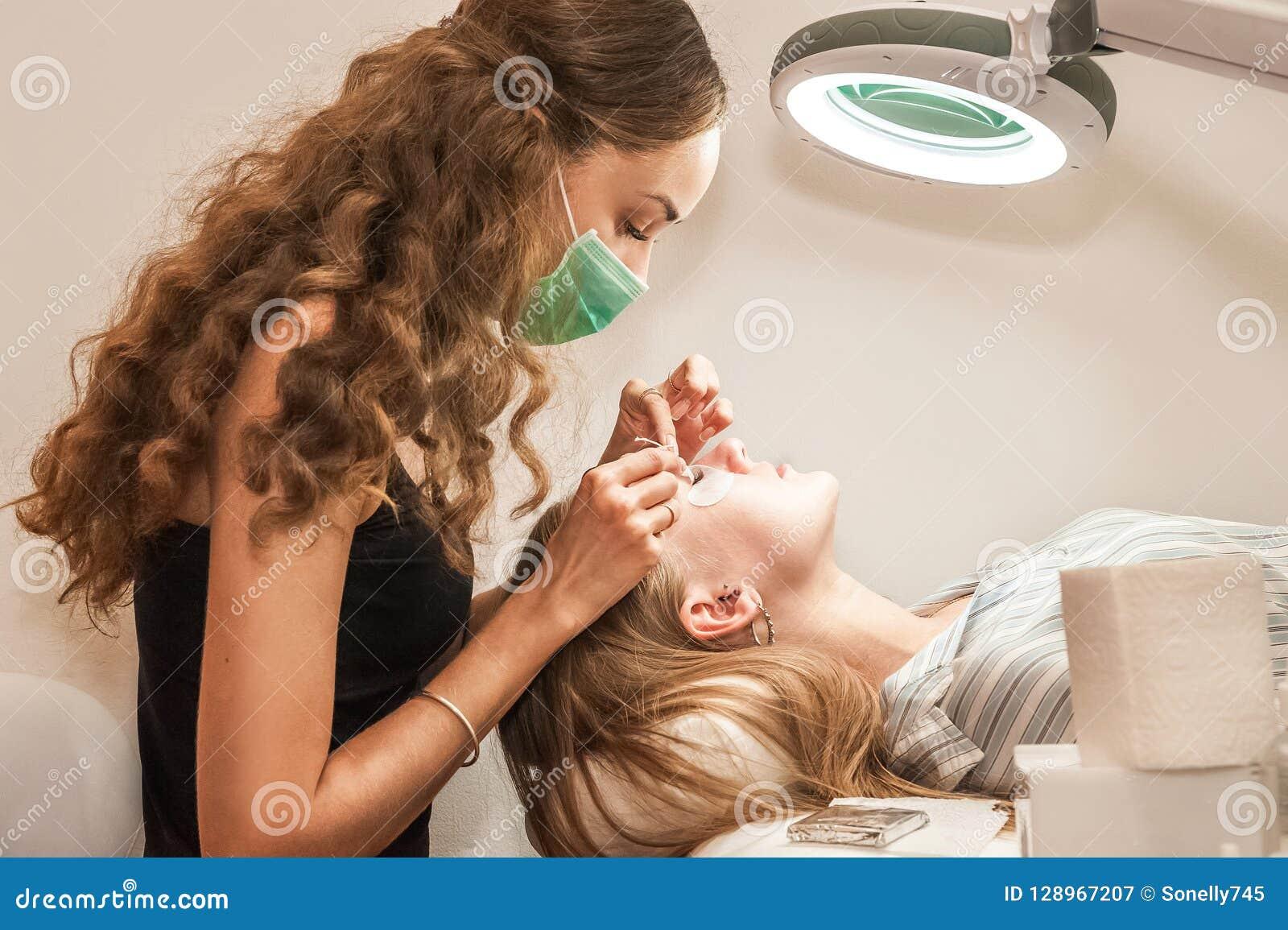 Dziewczyna w salonie wzrasta rzęsa klienta Proces rzęsy rozszerzenie w salonie