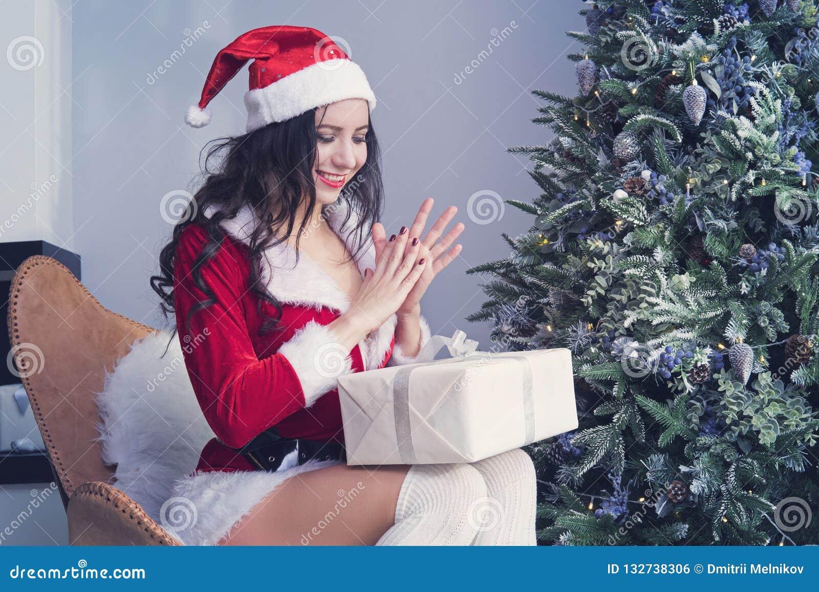 Dziewczyna w Santa kostiumu otwiera prezent w antycypacji, naciera jego ręki i klascze jego ręki, boże narodzenia, mas, zima, szc