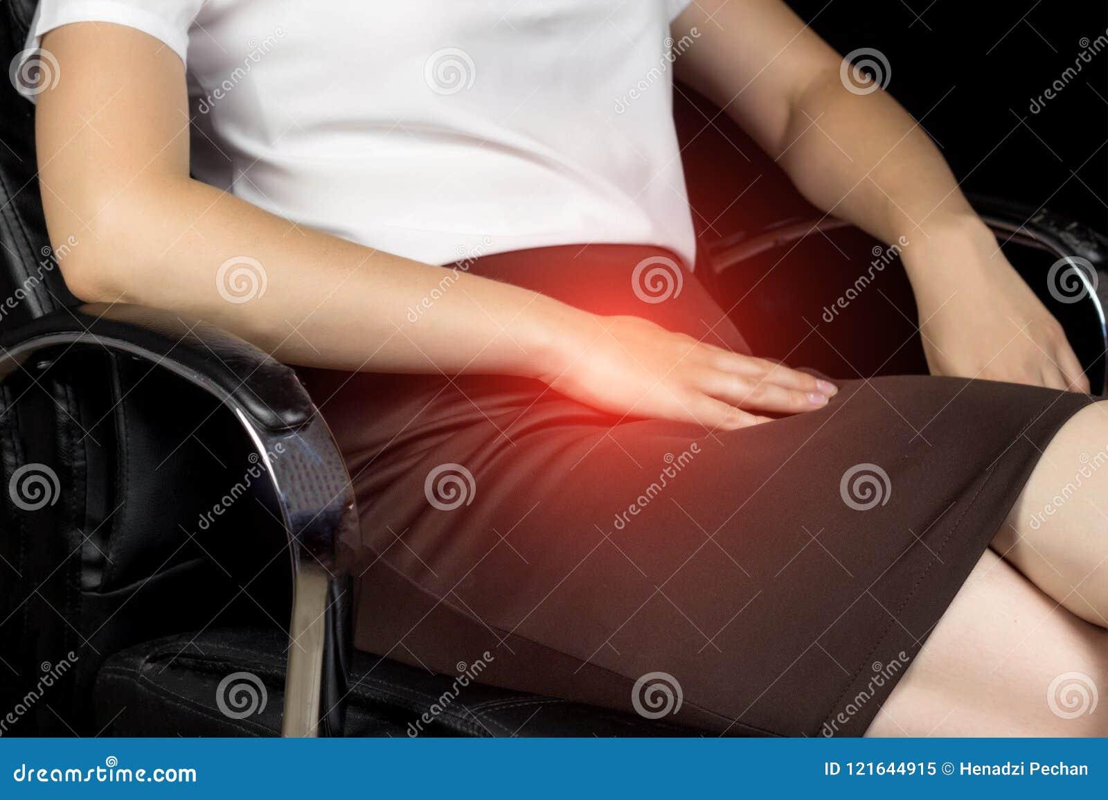 Dziewczyna w spódnicie siedzi na krześle i chwytach dalej pachwina teren, ból w niskim podbrzuszu, plciowa infekcja