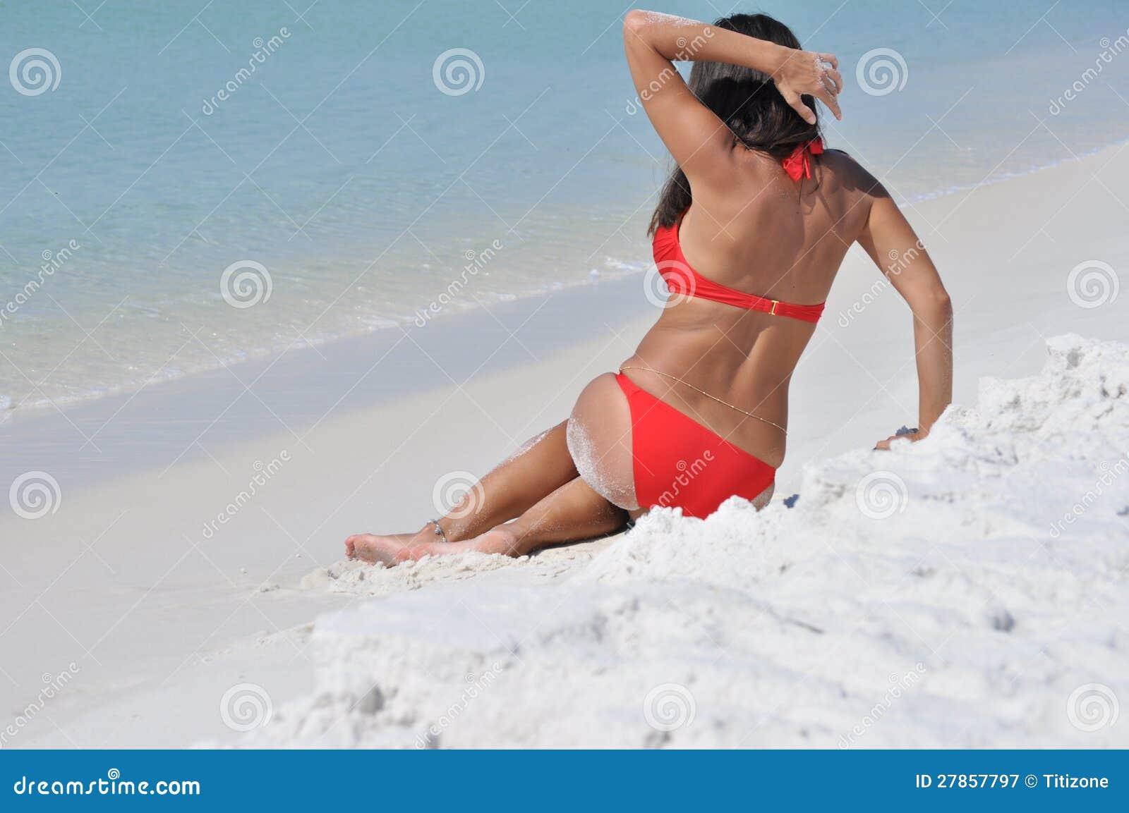 Dziewczyna w swimsuit obsiadaniu na plaży
