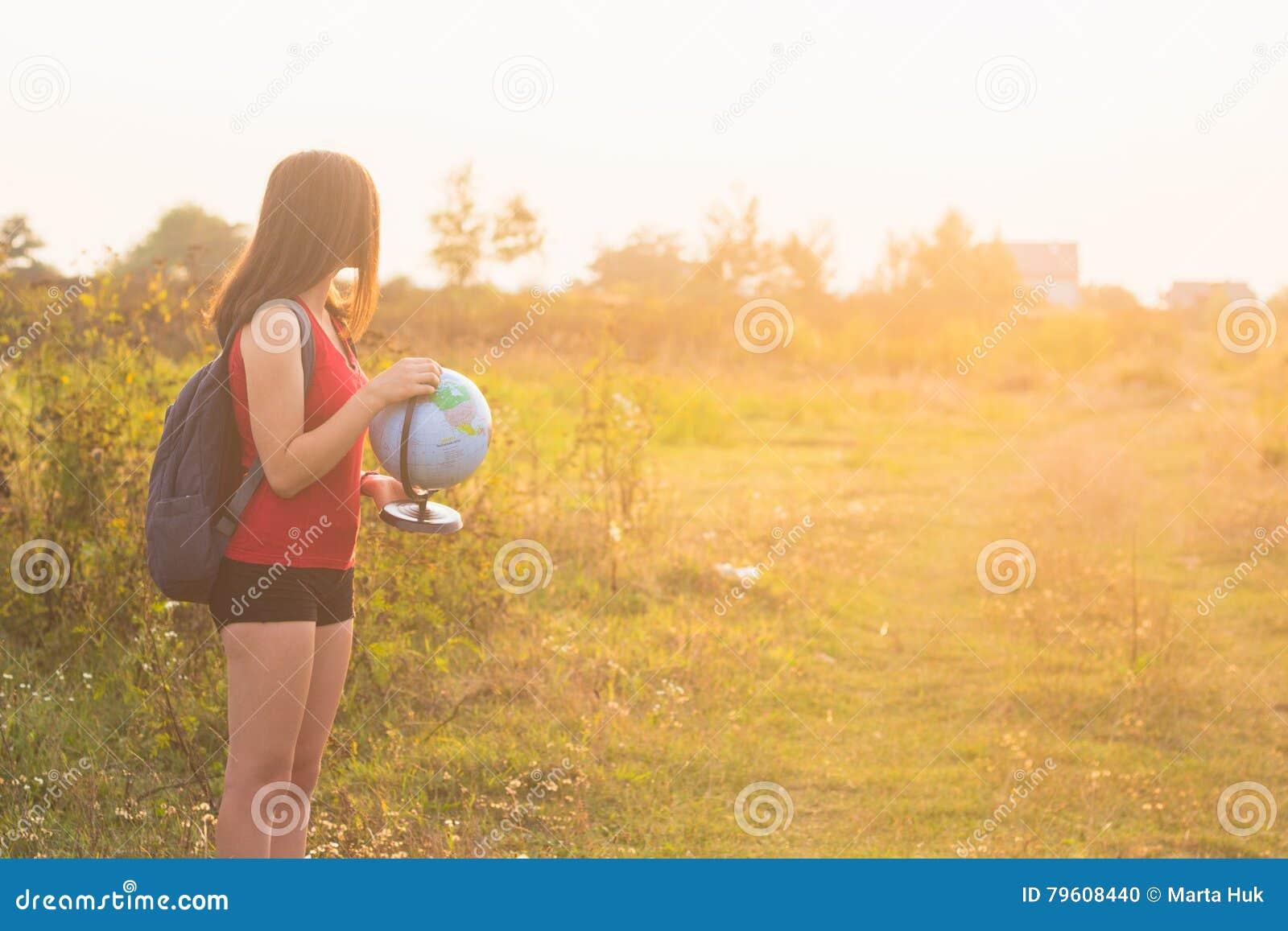 Dziewczyna z backback mienia kulą ziemską