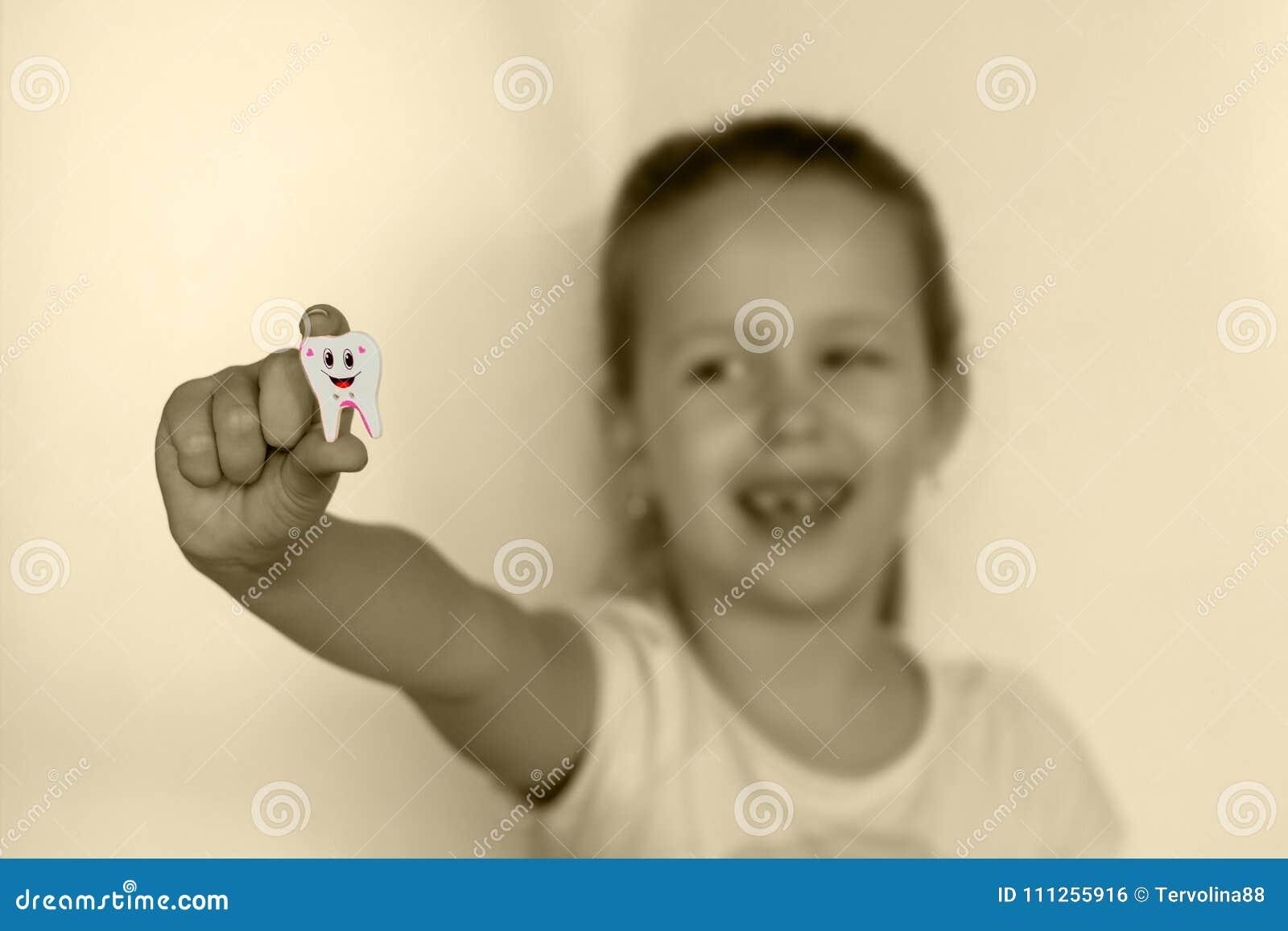 Dziewczyna z brakującym zębu zębem pokazuje zabawkę przy ręki ` s długością