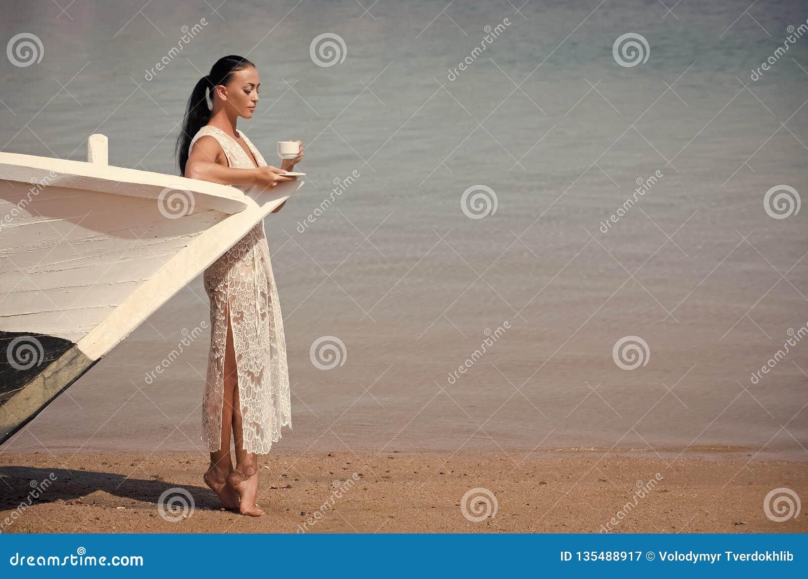 Dziewczyna z filiżanką przy łodzią