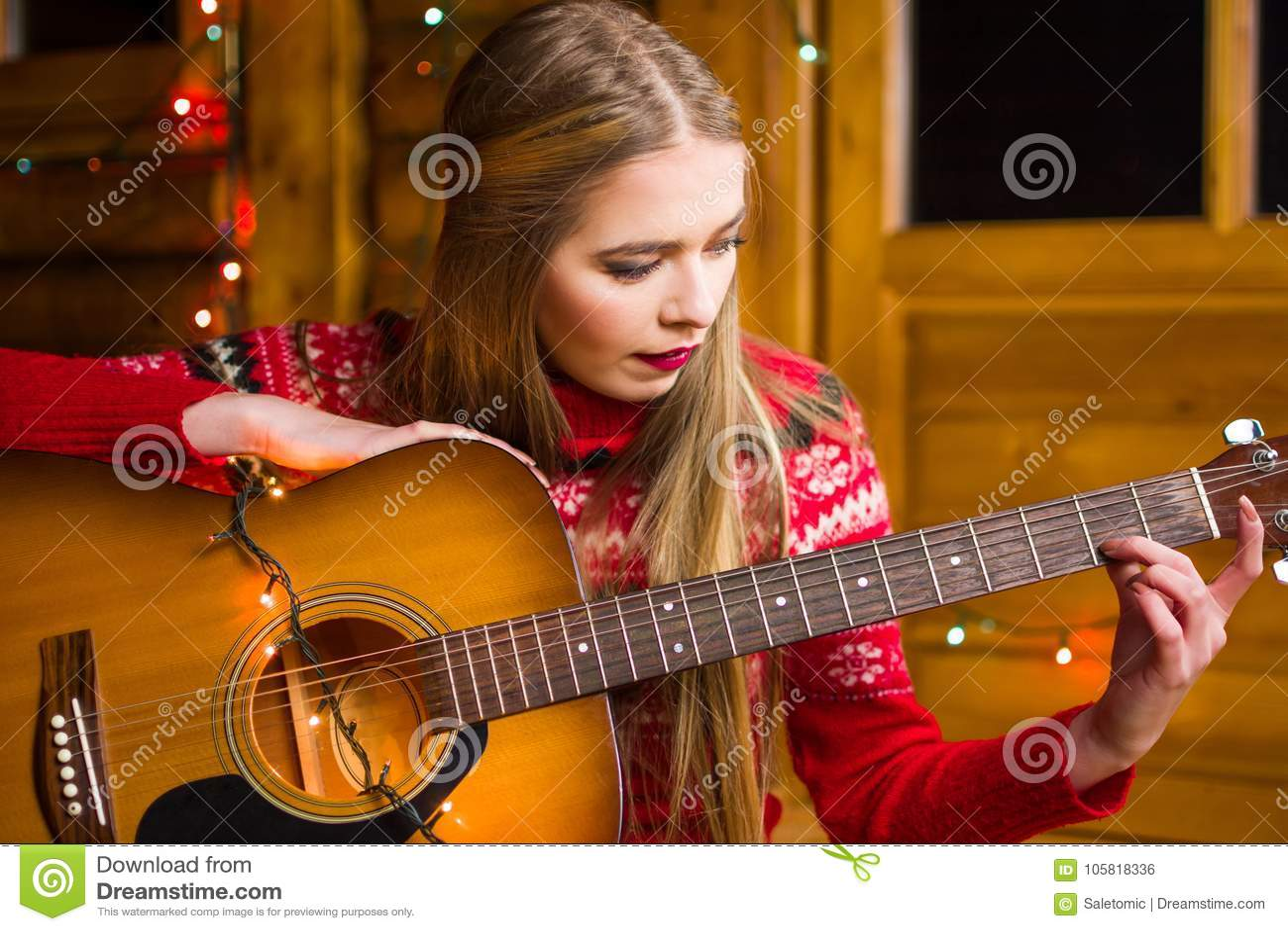 Dziewczyna z gitarą akustyczną w świątecznym środowisku