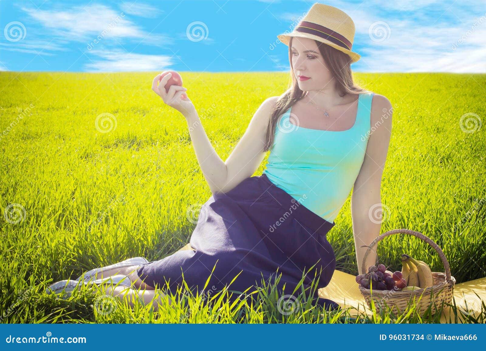 Dziewczyna z jabłkiem przeciw trawie i niebu