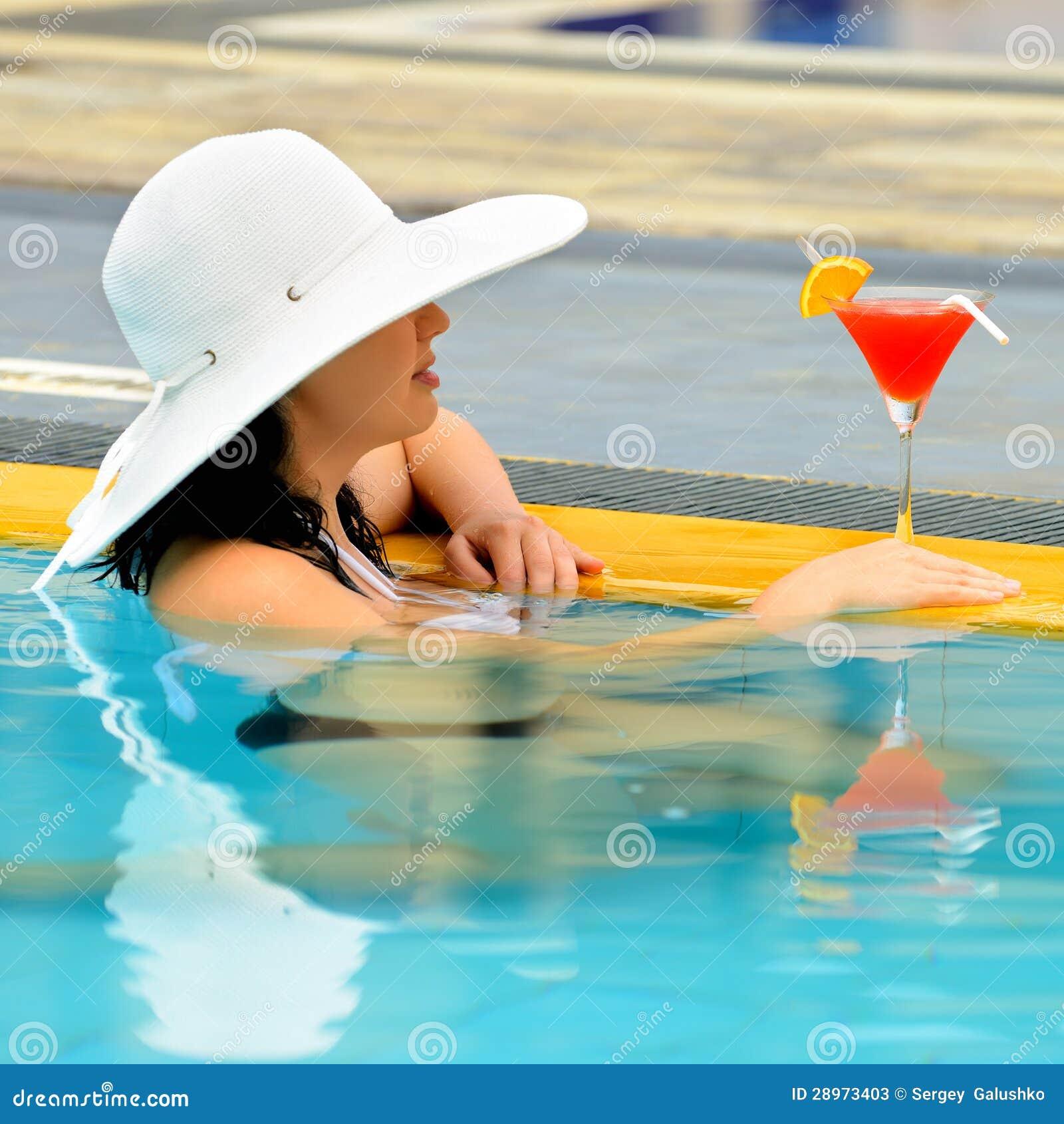 Dziewczyna z koktajlem przy krawędzią pływacki basen
