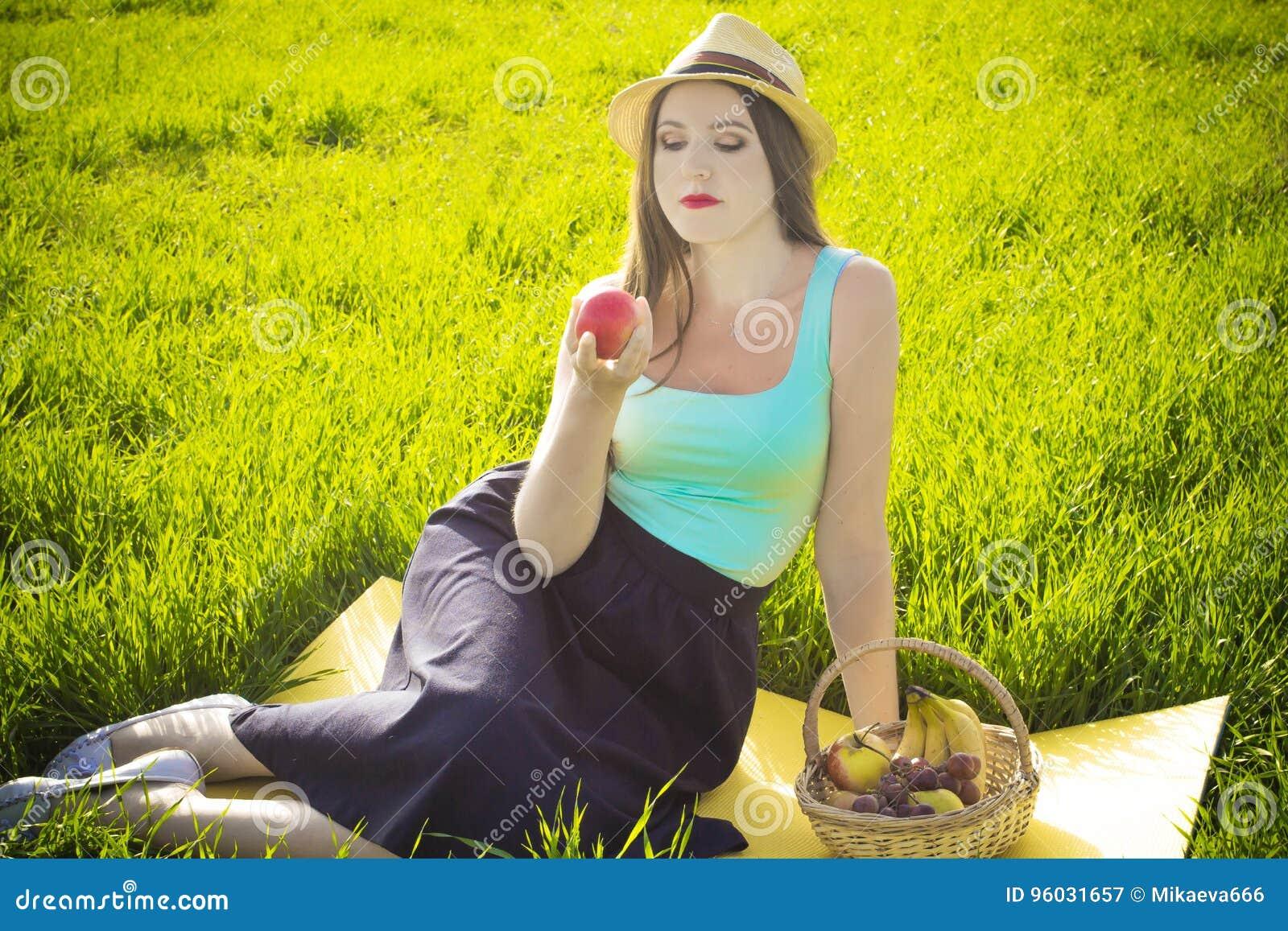 Dziewczyna z koszem je jabłka owoc